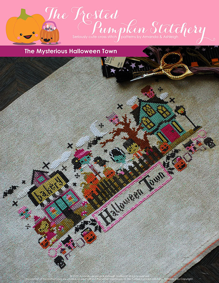 Mysterious Halloween Town counted cross stitch pattern. Bottom text says Halloween Town. The town has a witch in front of a bakery, a scarecrow among pumpkins, Frankenstein and his Bride next to a haunted house.