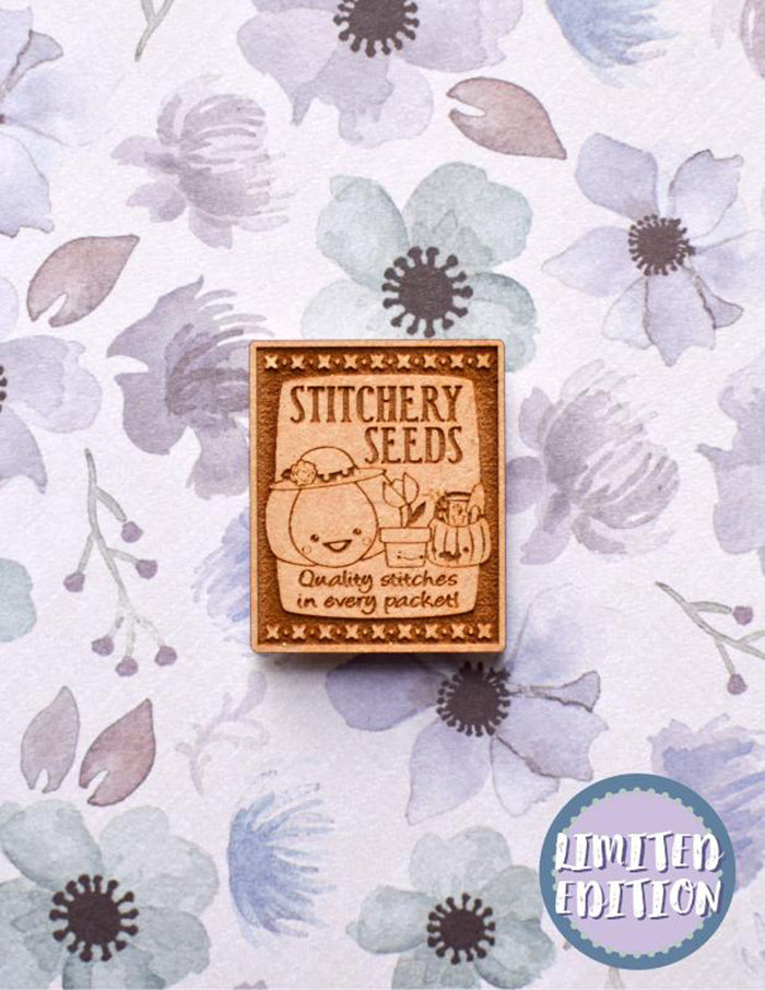 "Image of a wooden needleminder with a vintage seed packet. Text reads ""quality stitches in every packet""."