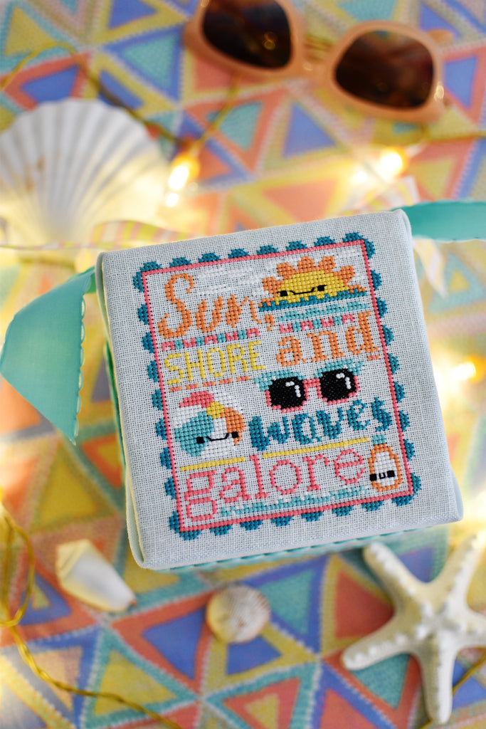 Waves Galore Counted Cross Stitch Pattern. Image of a kawaii sun, beach ball, sunglasses and sunscreen. Tropical colors including aqua, bright pink and oranges. Text in the chart reads Sun, Shore and Waves Galore. Background of the photo are sunglasses and seashells.