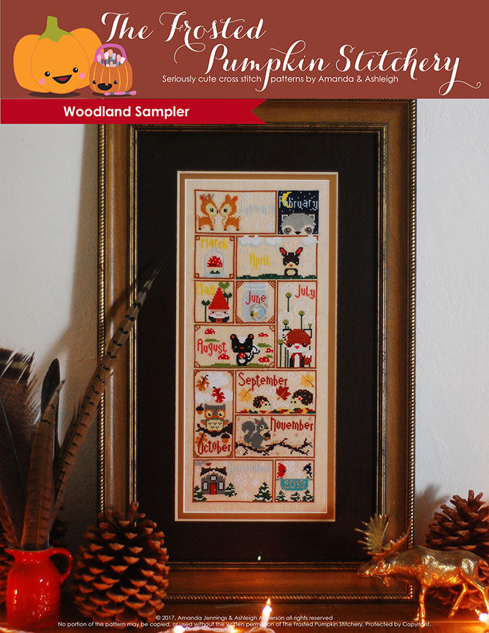 Woodland Sampler counted cross stitch pattern. Twelve animals with monthly calendar names in a brown frame with gold edges. Animals include deer, raccoon, skunk, fox, hedgehogs and squirrels.