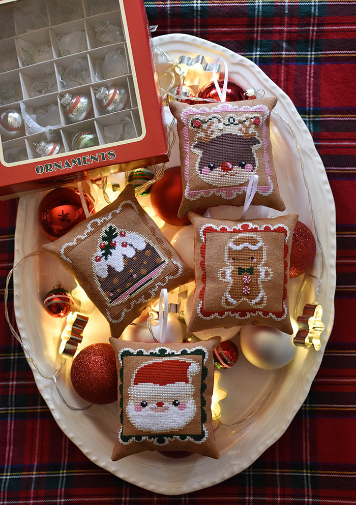 Cookies for Santa counted cross stitch pattern. Chubby ornaments are in a dish on a plaid tablecloth.