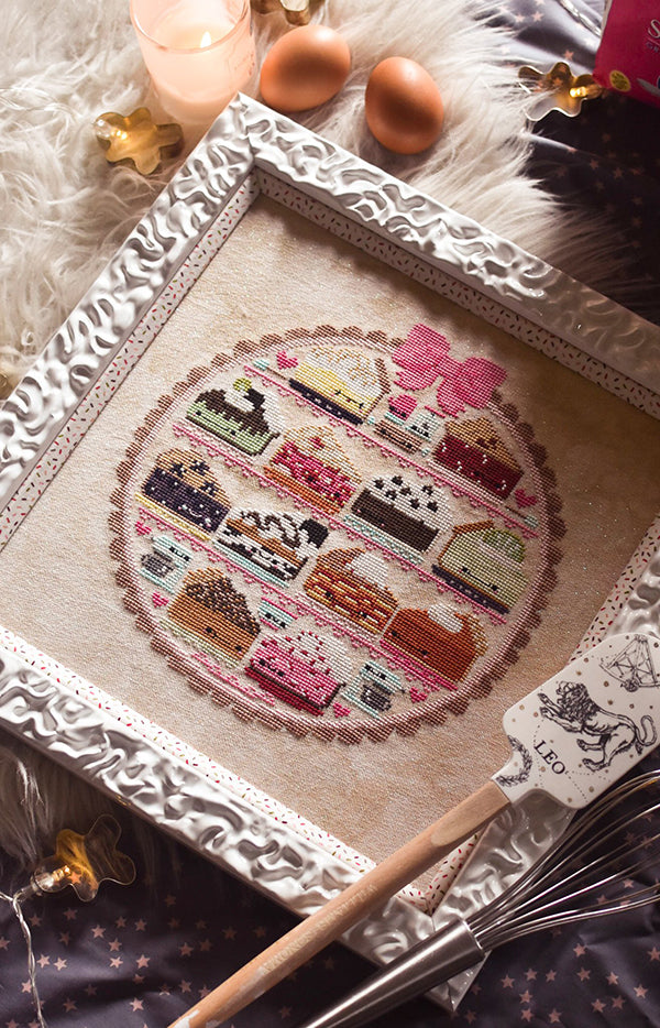 Sweet as Pie counted cross stitch pattern. Twelve kawaii pies cross stitch pattern in a white frame surrounded by baking supplies. Flay lay on a fake fur rug with eggs.