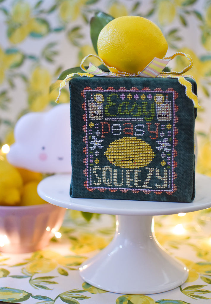 Easy Peasy Counted Cross Stitch Pattern. Image of a sour faced lemon stitched on green fabric with the text Easy Peasy above the lemon and below the word Squeezy. A background of lemons.
