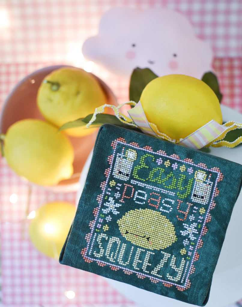 Easy Peasy Counted Cross Stitch Pattern. Image of a sour faced lemon stitched on green fabric with the text Easy Peasy above the lemon and below the word Squeezy. Image background is pink gingham, a little cloud and a bowl of lemons.