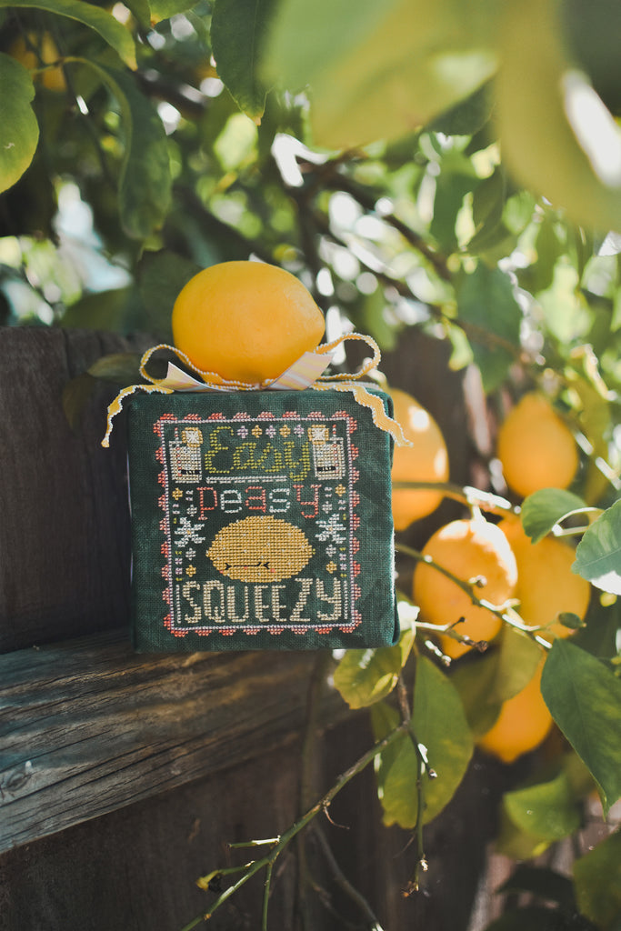 Easy Peasy Counted Cross Stitch Pattern. Image of a sour faced lemon stitched on green fabric with the text Easy Peasy above the lemon and below the word Squeezy. Photo taken on a summer morning with glow-y light and a lemon tree in the background.