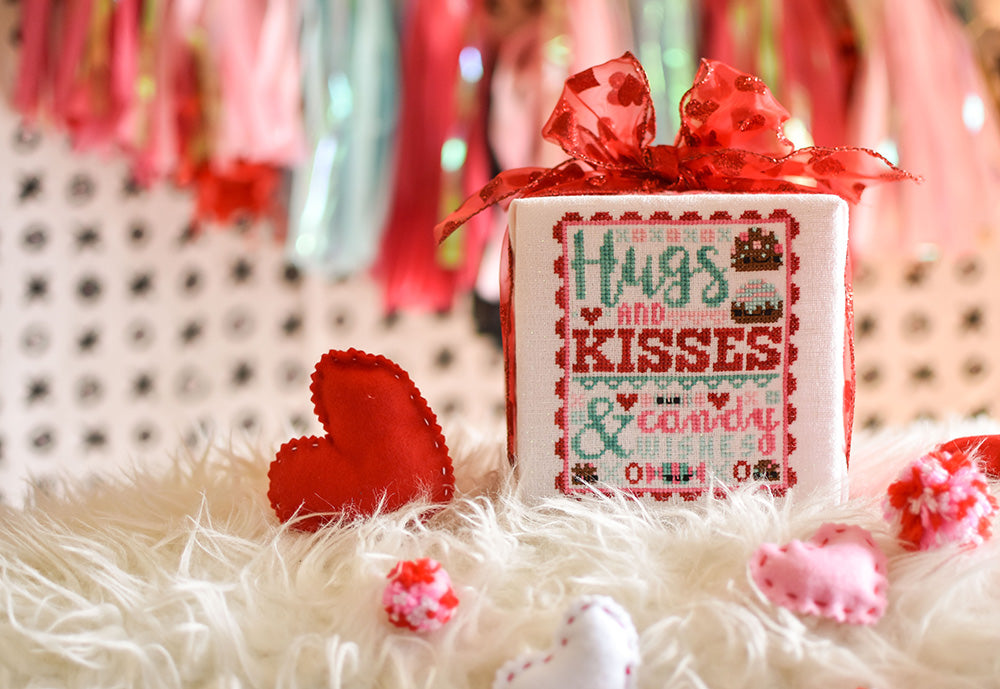 "Hugs and Kisses counted cross stitch pattern. Valentine's Day cross stitch pattern surrounded by felt hearts. Text reads ""Hugs and kisses and candy wishes"""