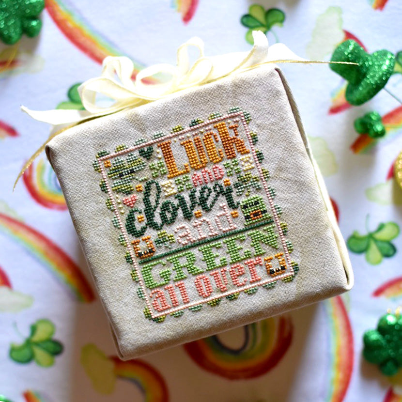 "Luck and Clover counted cross stitch pattern. St. Patrick's Day inspired with pinks, golds, dark and light green. Text reads ""Luck and Clover and Green All Over"". Finished project is laying on a rainbow background."