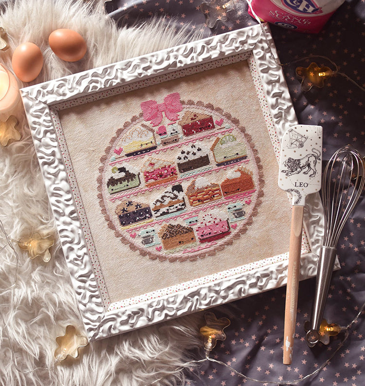 "Sweet as Pie counted cross stitch pattern. Twelve kawaii pies cross stitch pattern in a white frame surrounded by baking supplies. Flat lay on a gray background with a spatula that reads ""Leo""."