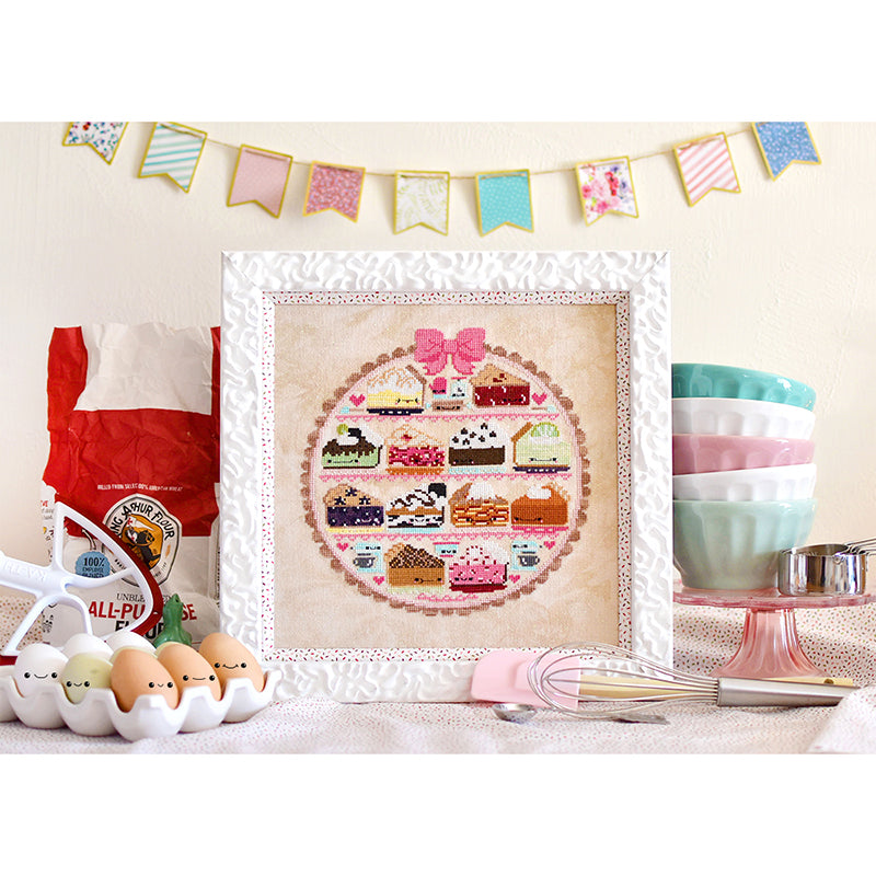 Sweet as Pie counted cross stitch pattern. Bunting in the background with bowls stacked on a cake tray and a bag of flour.