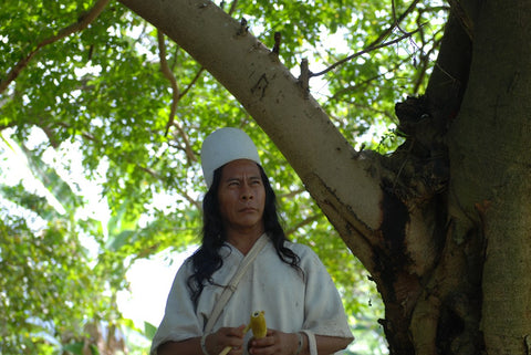 Mamo Camilo holding a gourd and stick for sacred coca medicine