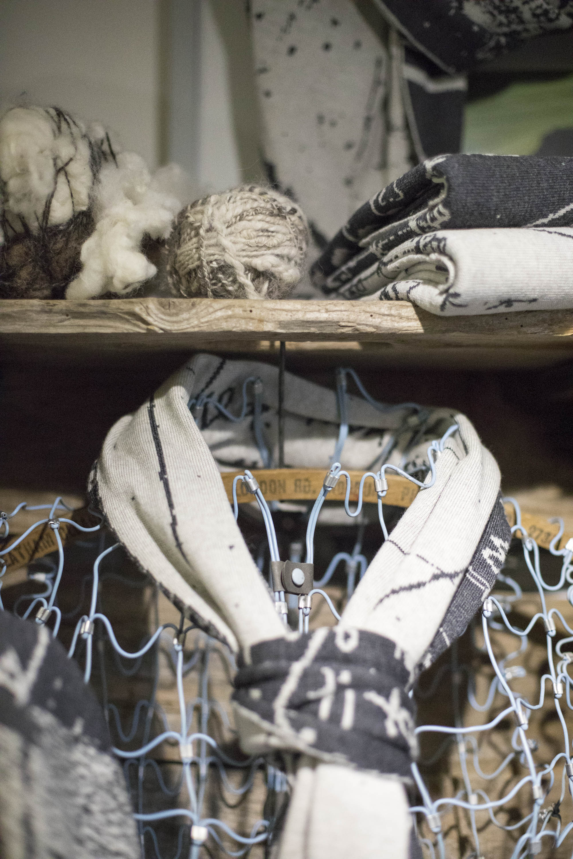 Contemporary knitwear studio in the Shetland Islands, Scotland. Handspun yarn, a charcoal and stone white scarf on a wire frame mannequin, rustic shelving