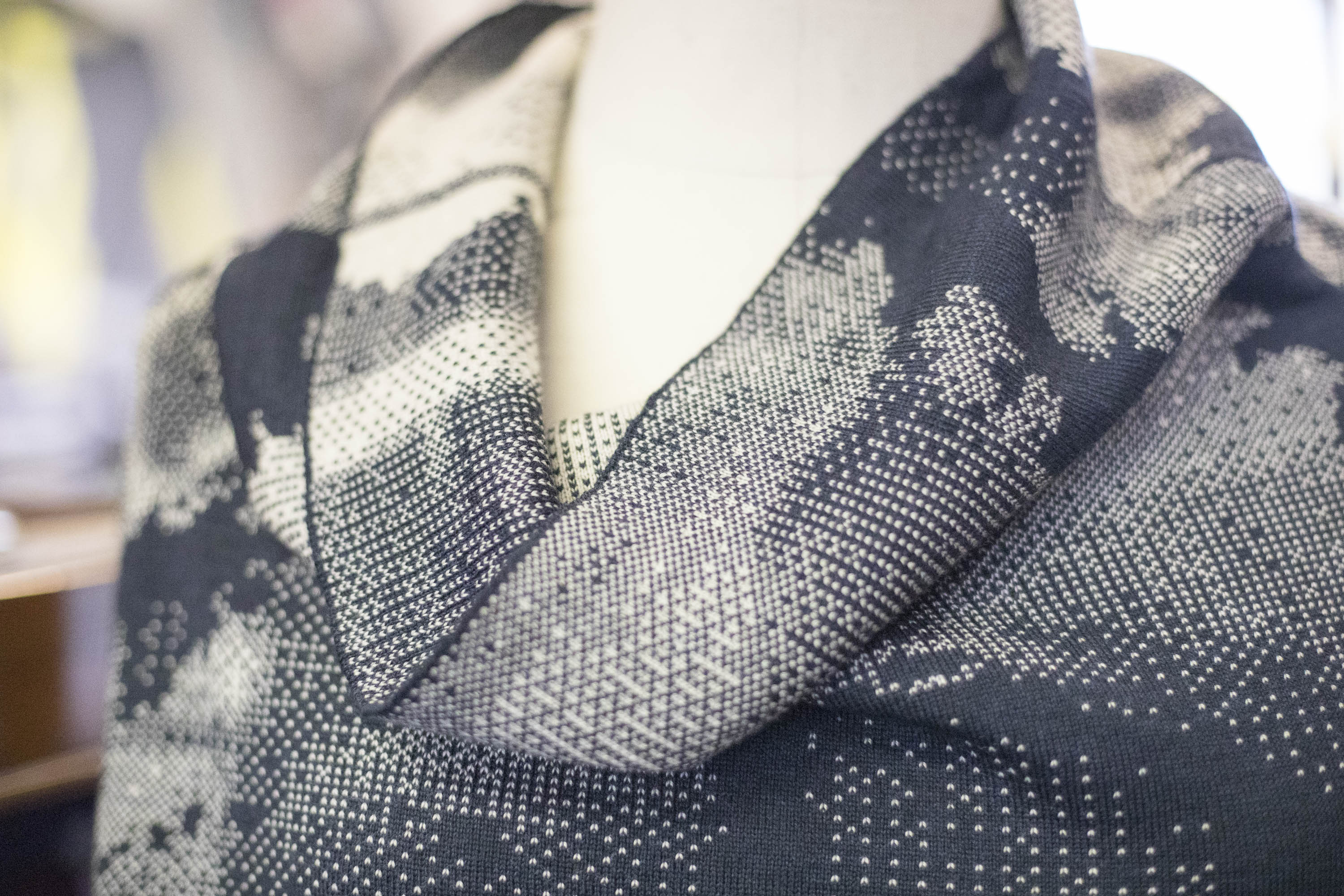 Detail of a contemporary Scottish knitted jumper. Cowl neck in inky blue and antique white, with abstract patterning