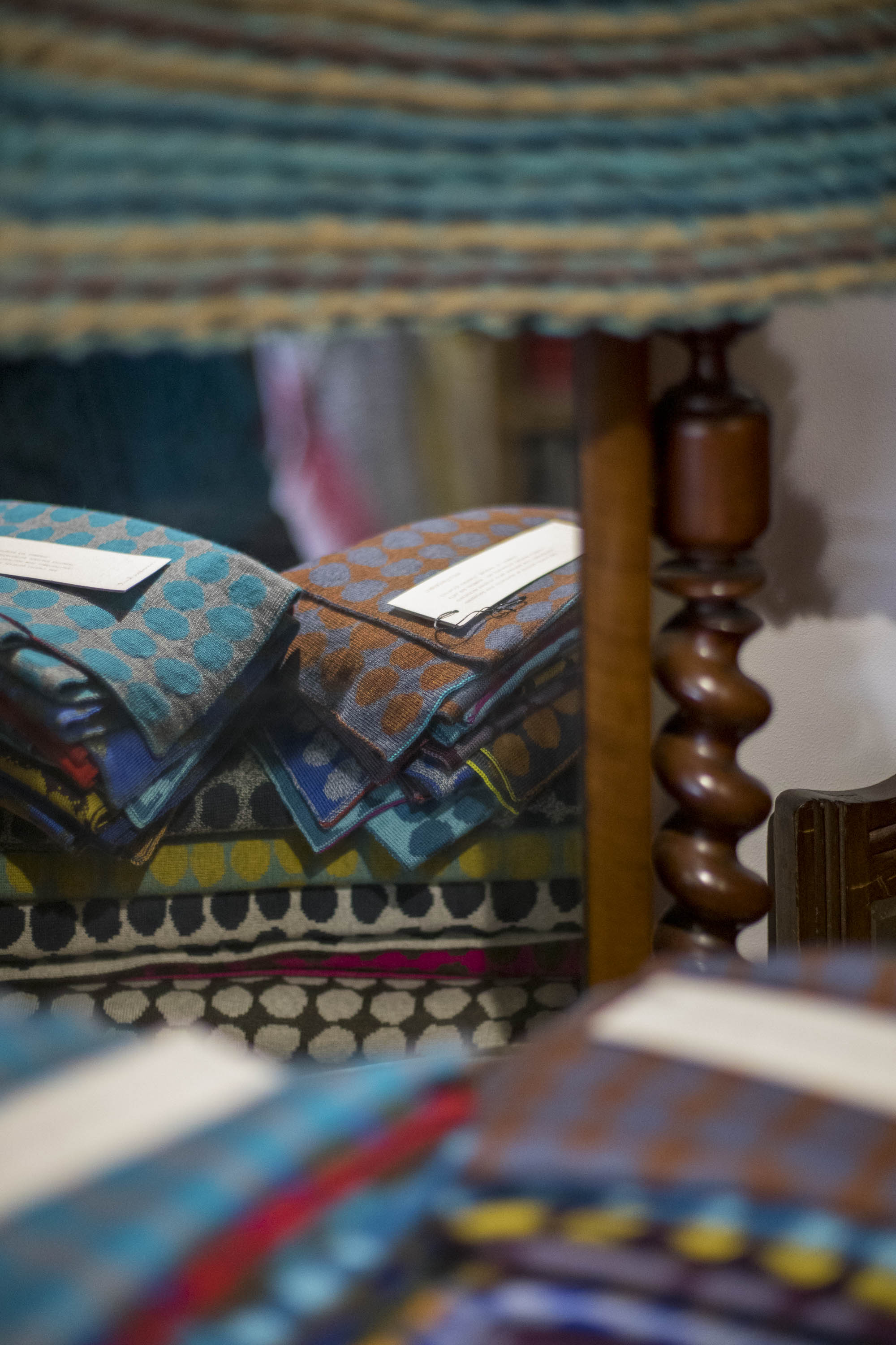 Stacks of contemporary knitwear on antique furniture in the Nielanell studio shop, Shetland