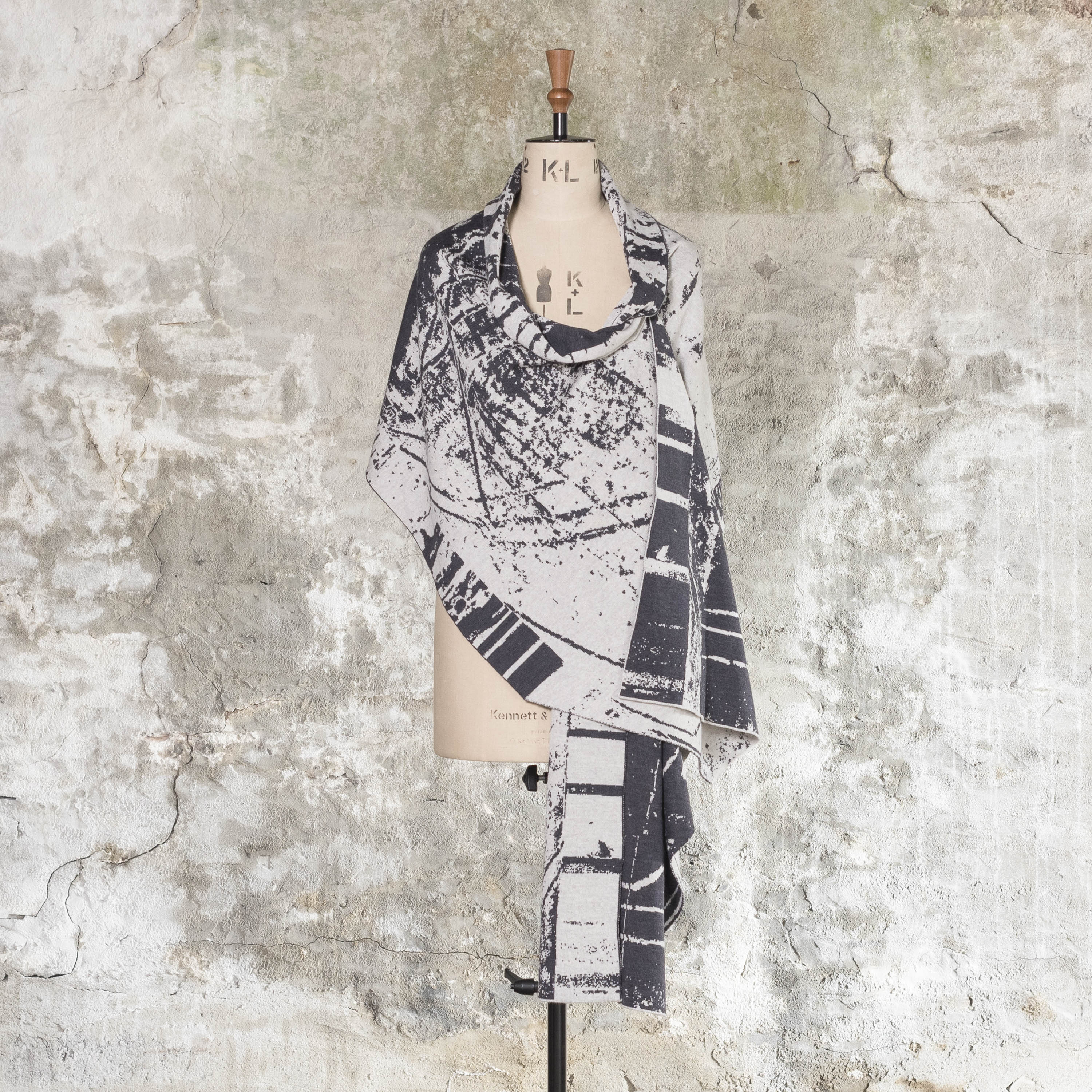 Contemporary Shetland shawl in Nielanell Byre abstract design, in charcoal and stone white yarn. Shown on a vintage mannequin against a rustic wall