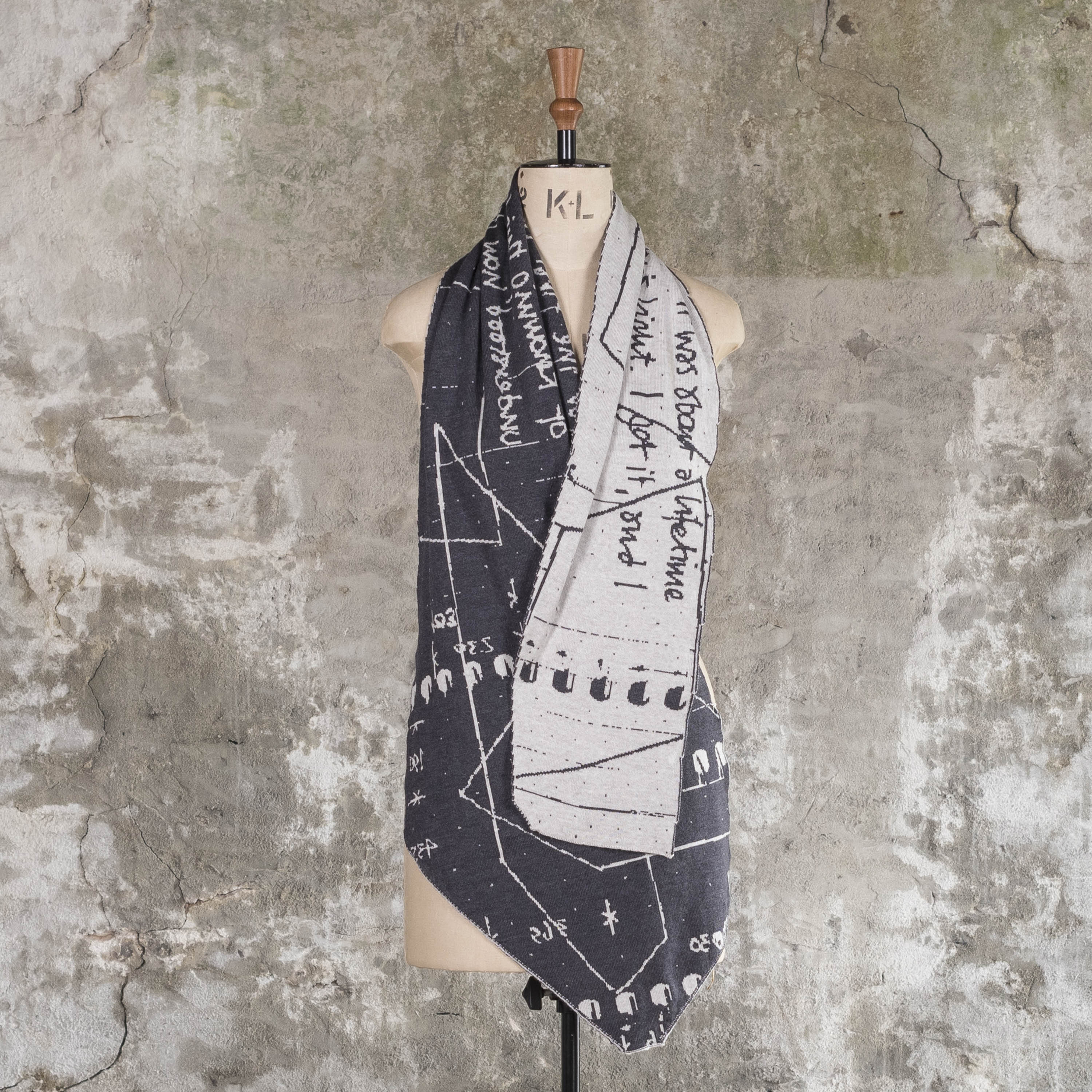 Contemporary, irregular shaped scarf with abstract pattern, knitted in charcoal grey and stone white. Shown on vintage mannequin against Shetland rustic wall.