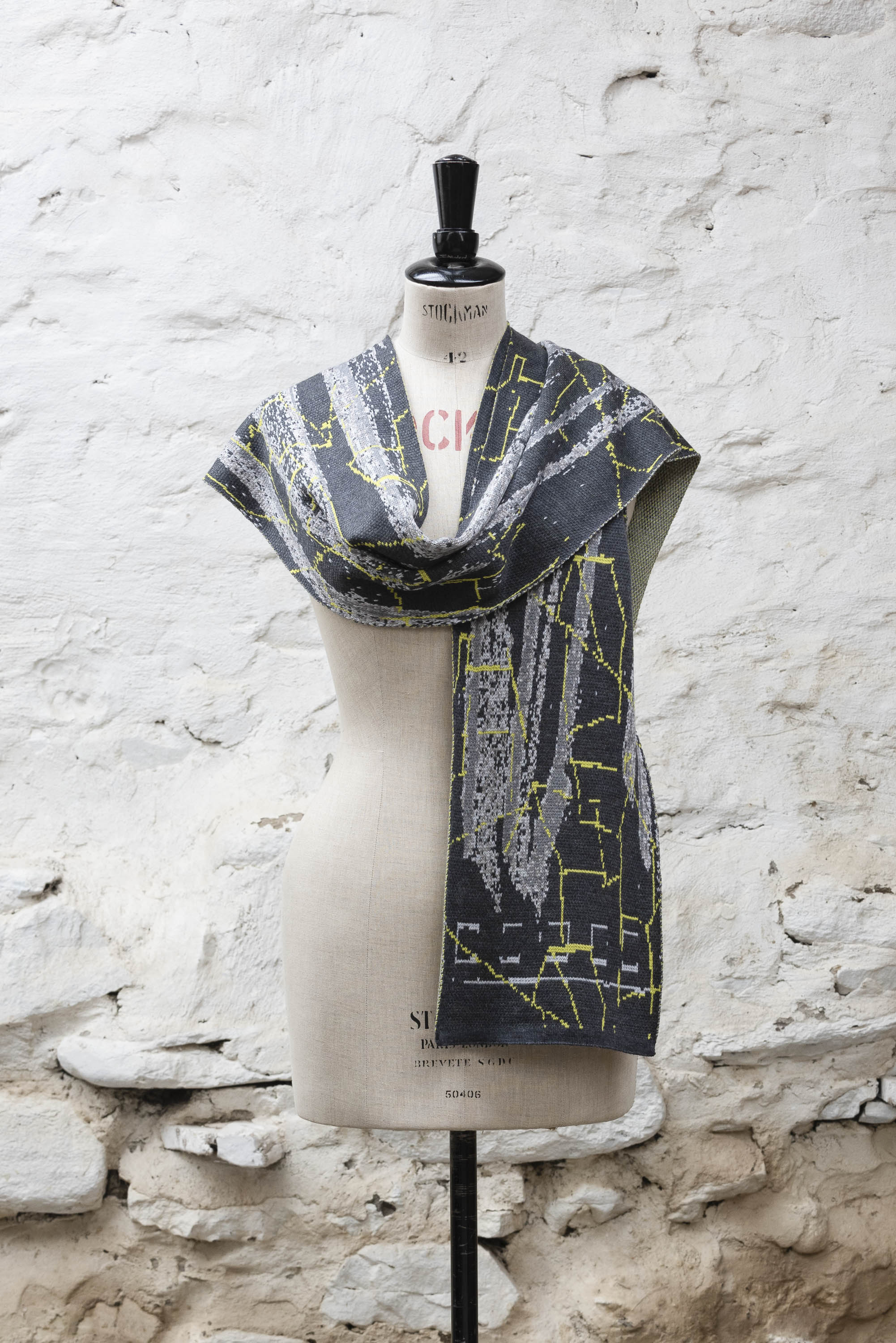 Contemporary Scottish knitted scarf with abstract pattern in greys with fluoro yellow highlights