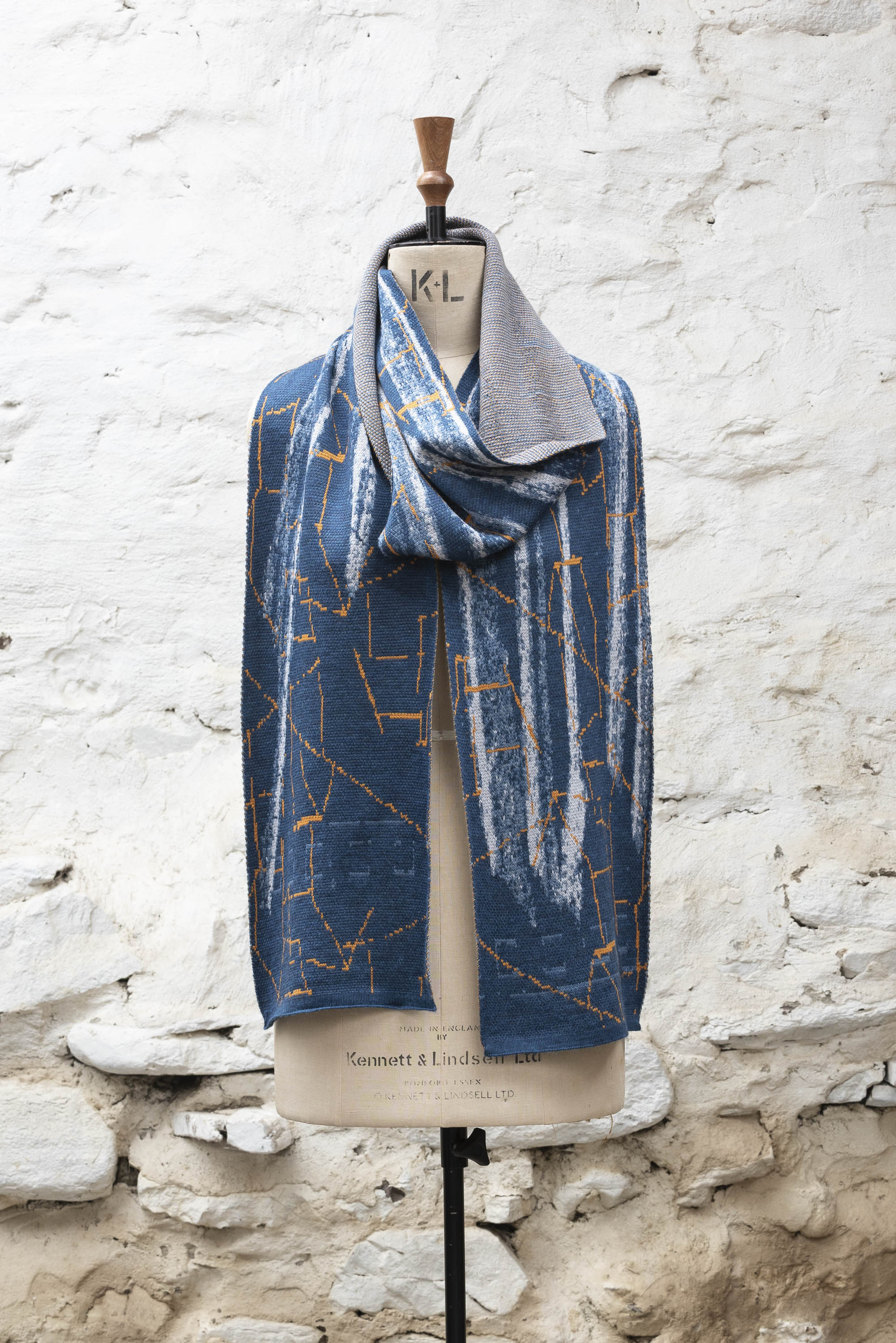 Contemporary Shetland knitted scarf in abstract design of blues and greys with orange highlights