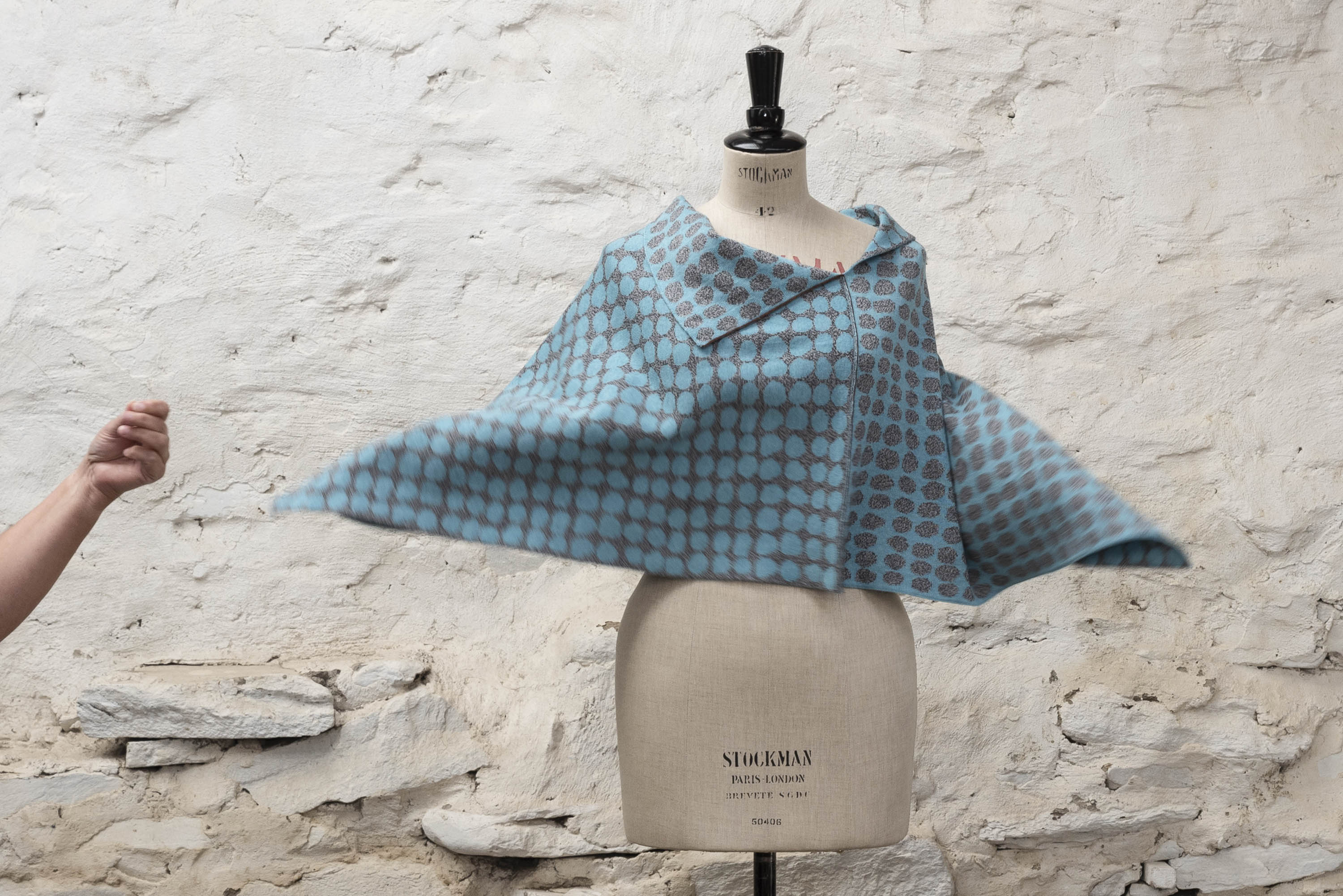 Modern knitted cape in abstract pebble-inspired design. Blue and grey colourway shown on a vintage mannequin, spinning.