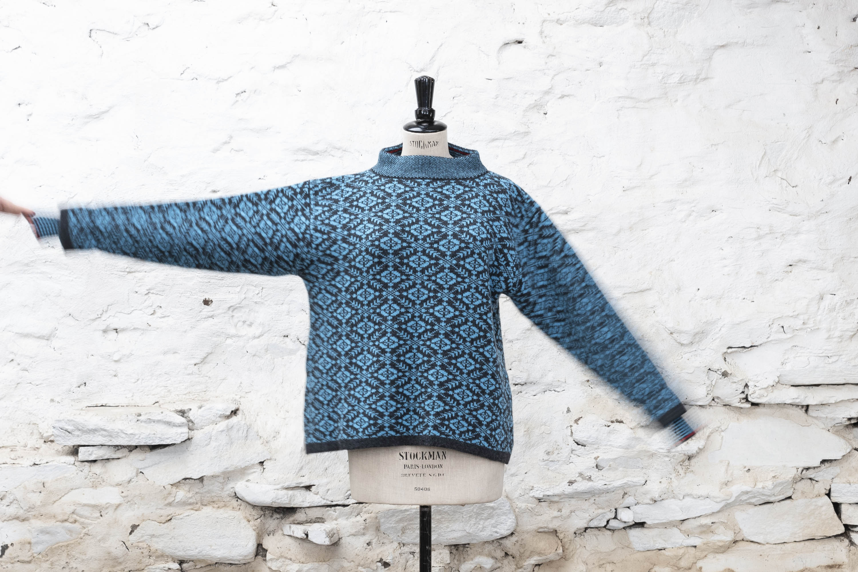 Fair Isle jumper in a bright turquoise and navy. Front view against a white-washed wall, with the right arm held up.
