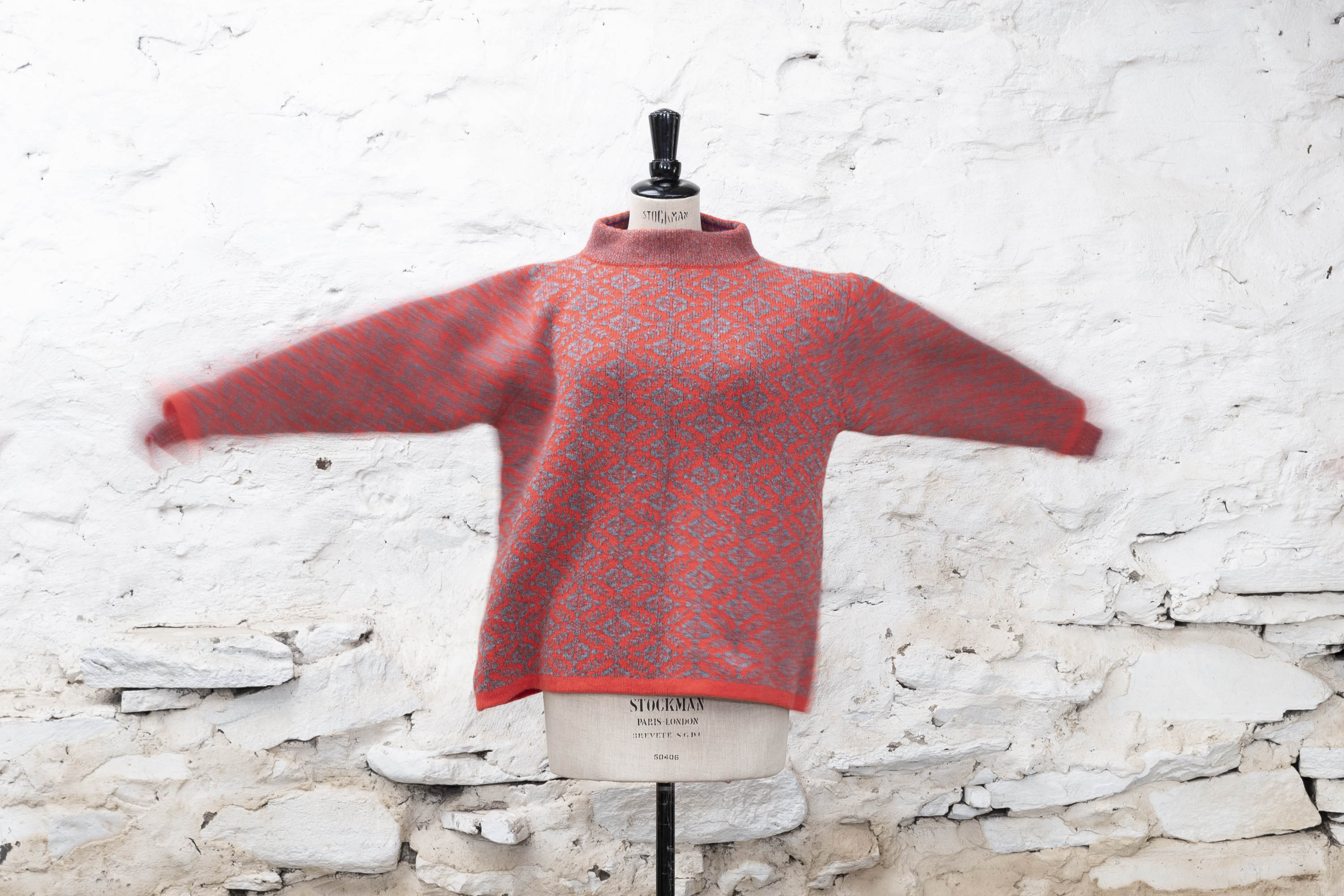 Shetland Smookie jumper with all-over Fair Isle pattern. Shown in coral and grey, on a spinning vintage mannequin - sleeves fly out.