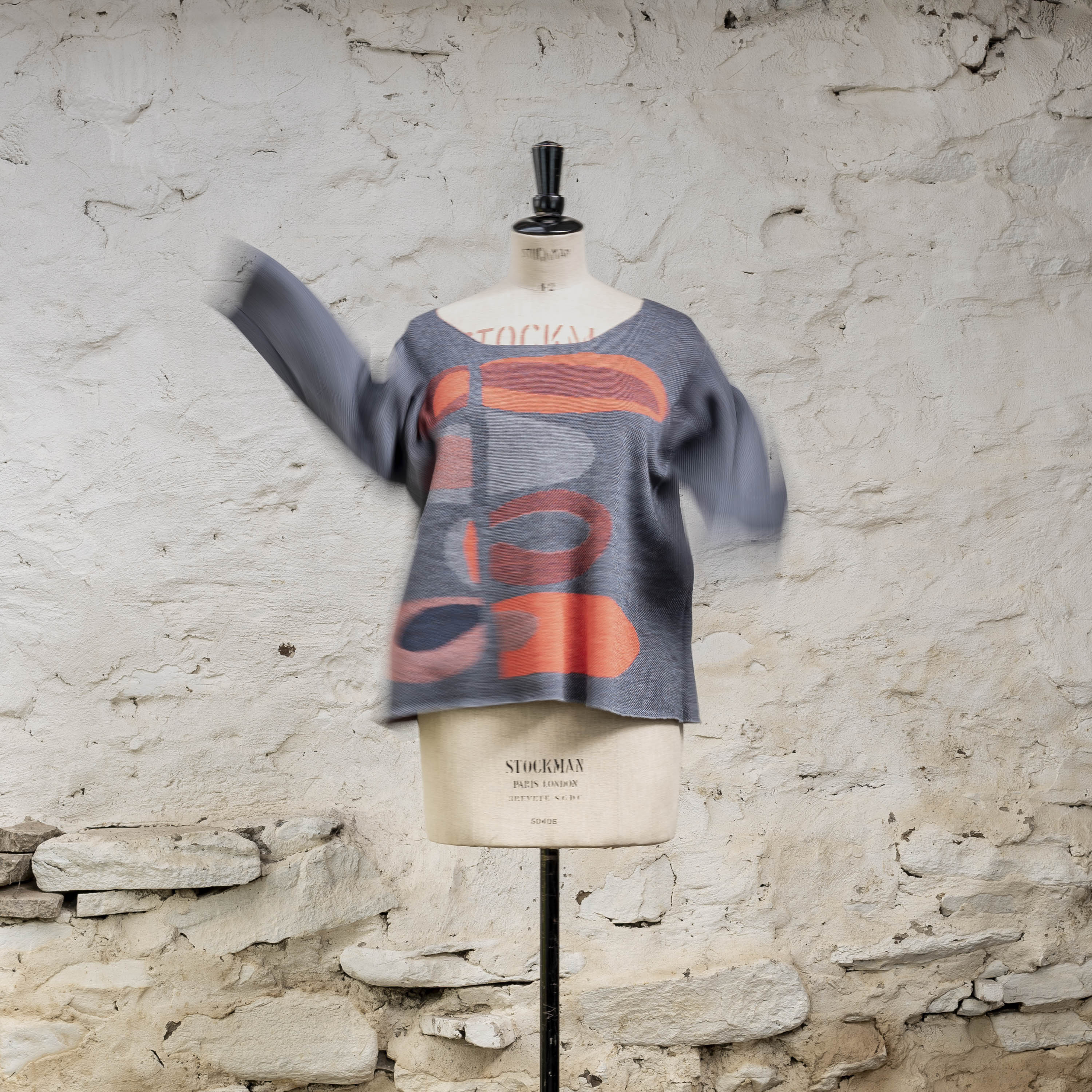 Contemporary Scottish knitwear, jumper in abstract mid-century inspired pattern. Coral and blues knitted in extra-fine merion