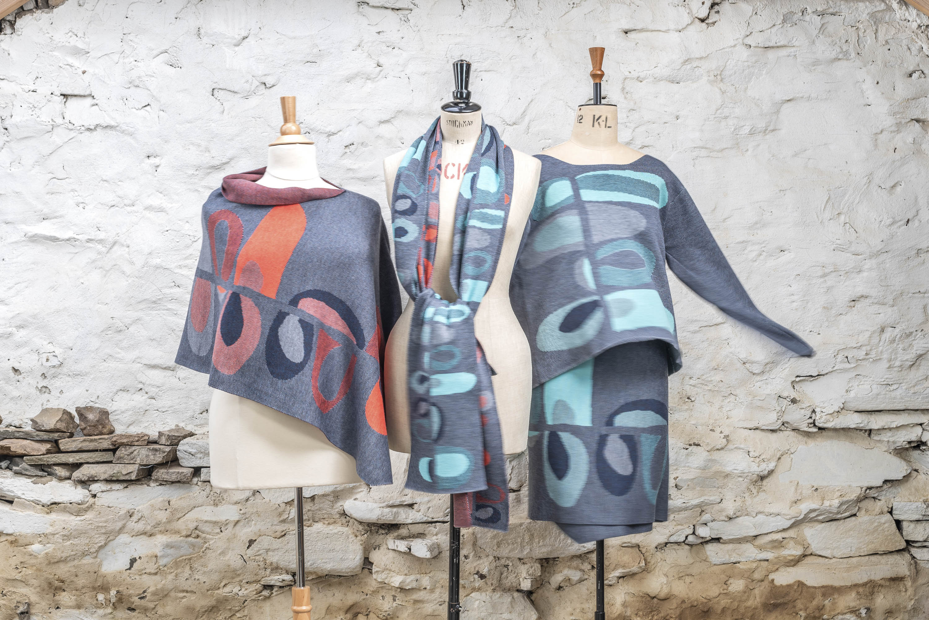 Contemporary Scottish knitwear, shown on a group of three mannequins. Abstract, curvilinear motifs in two colourways: coral and blues in a cape and scarves, skirt and jumper in aqua and blues