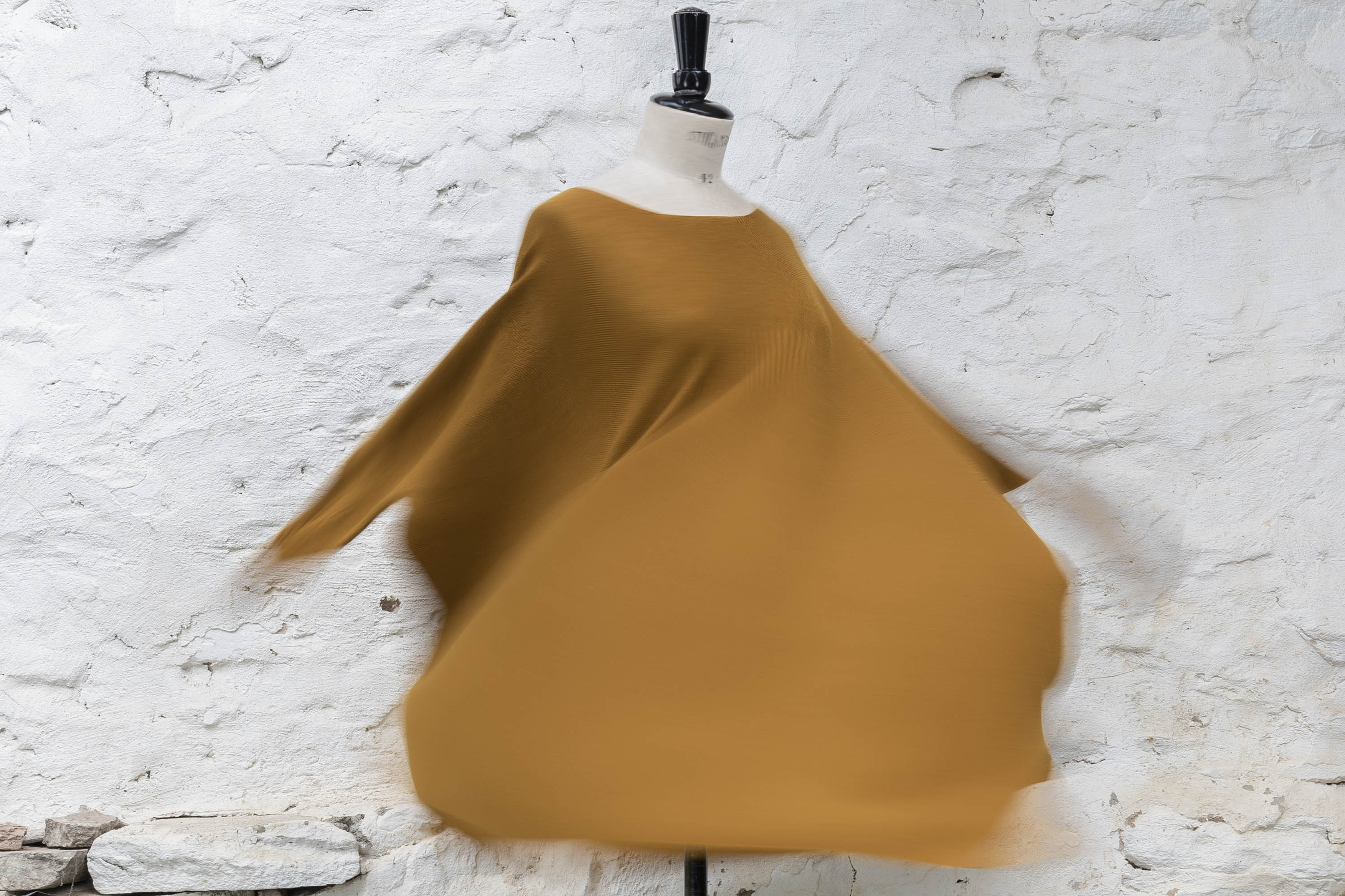 Lightweight contemporary merino sweater made in Scotland. Ochre yellow, on a mannequin being spun to show relaxed shape