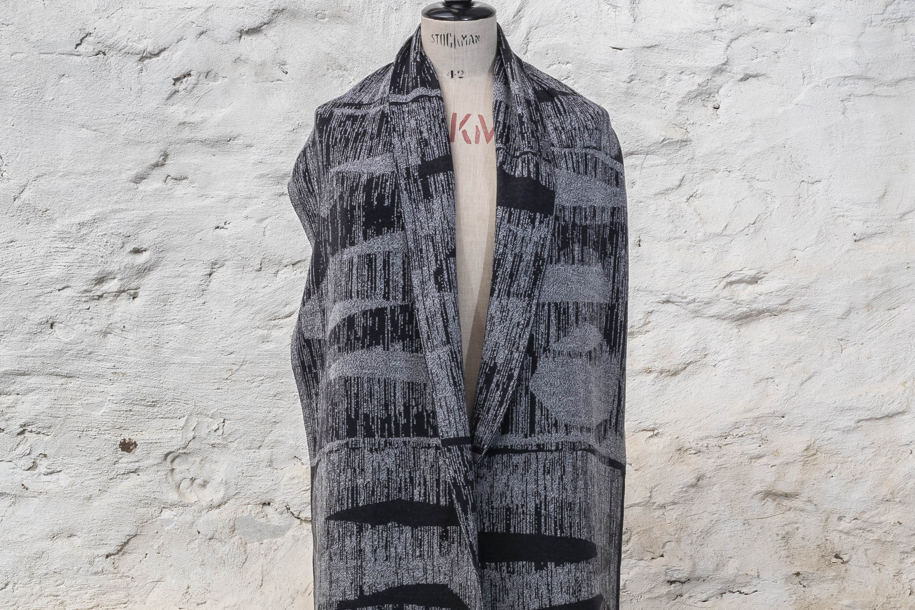 Contemporary, abstract knitted scarf in greys with linear, mid-century motif