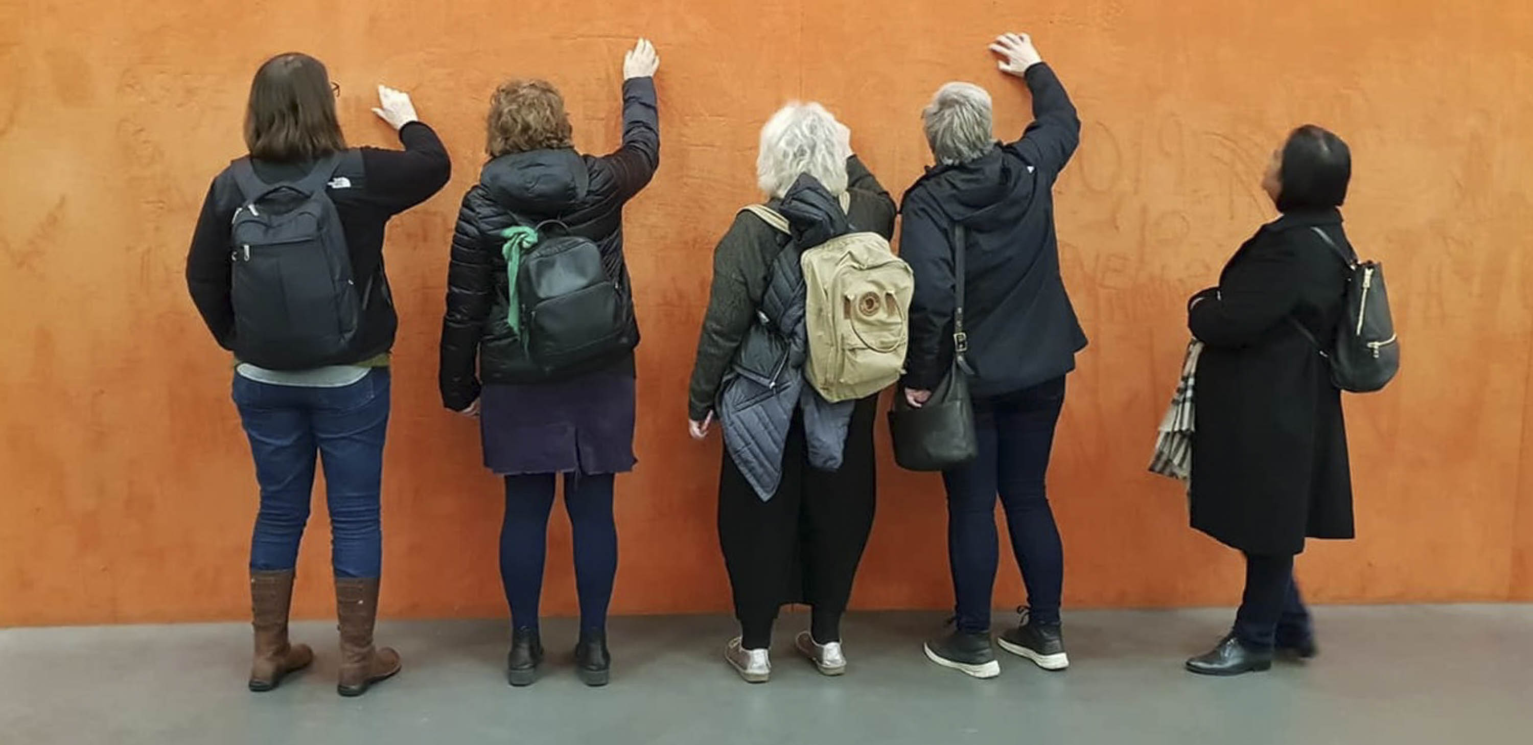 Five women stand with their backs to the camera, drawing with their fingers on a wall covered with orange pigment