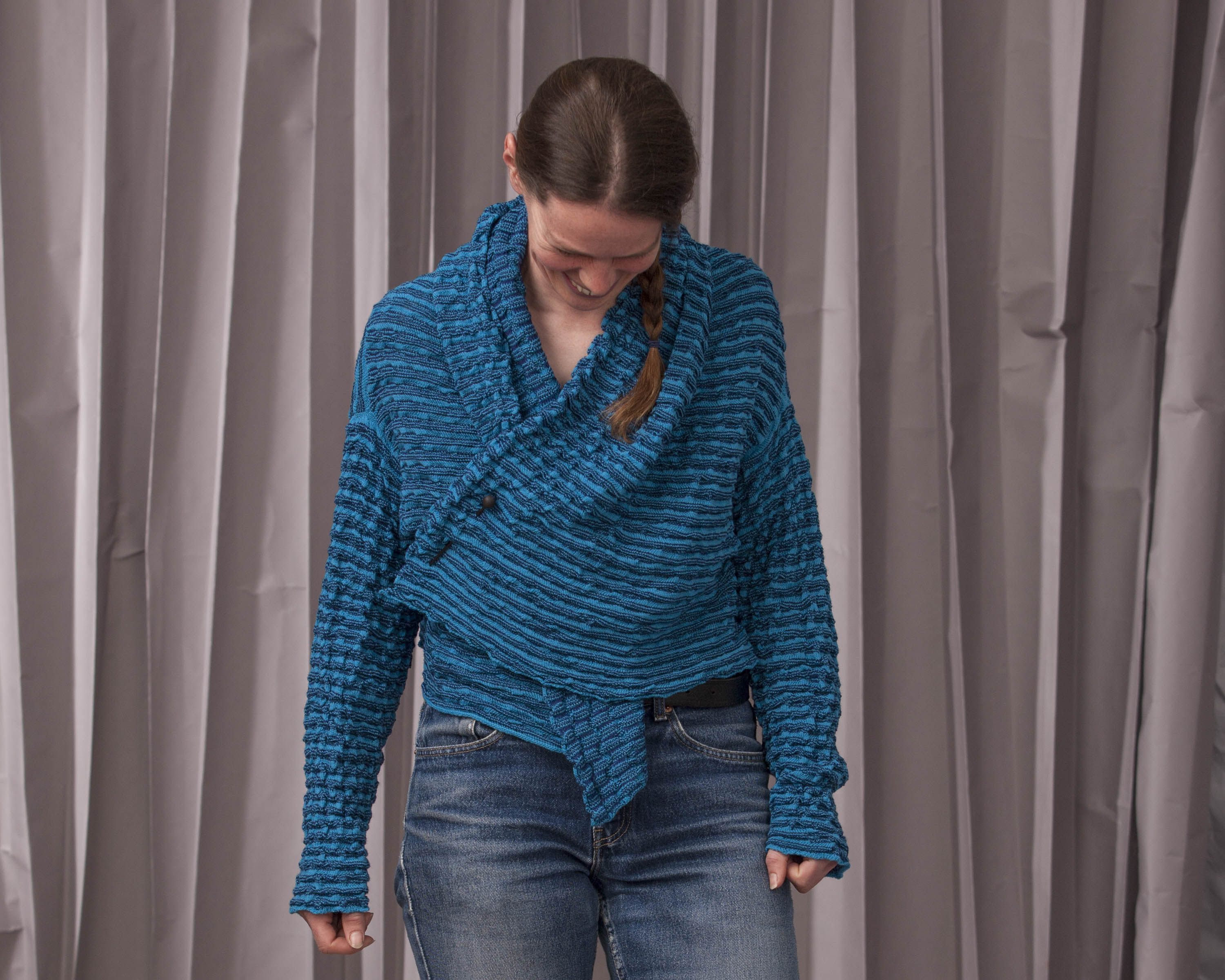 Model wears a contemporary knitted open jacket in bright blue, softly ridged textile