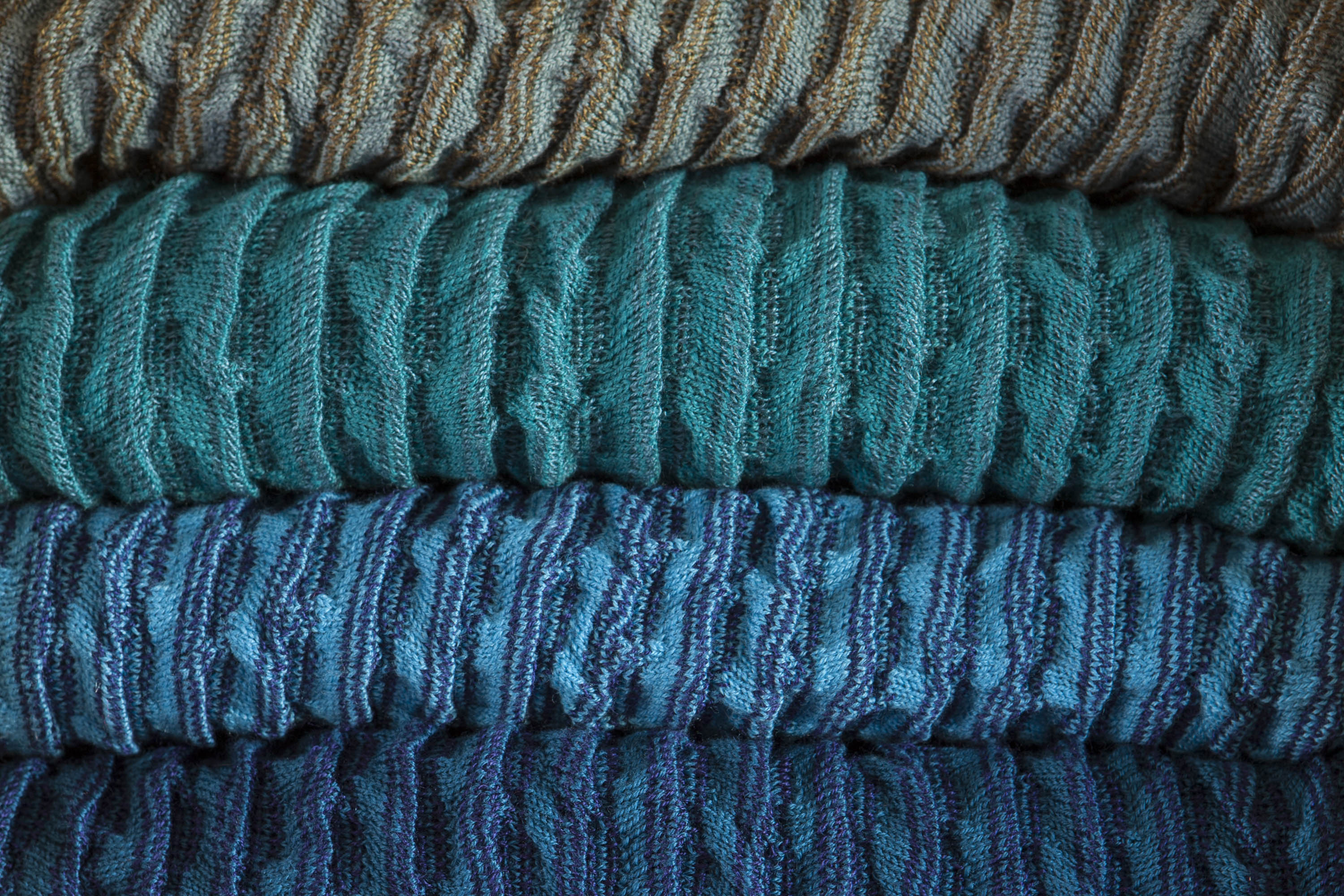A close up of stacked Rigg Vaarie jackets - ridged knitwear in blues. At the Nielanell studio, Hoswick, Shetland