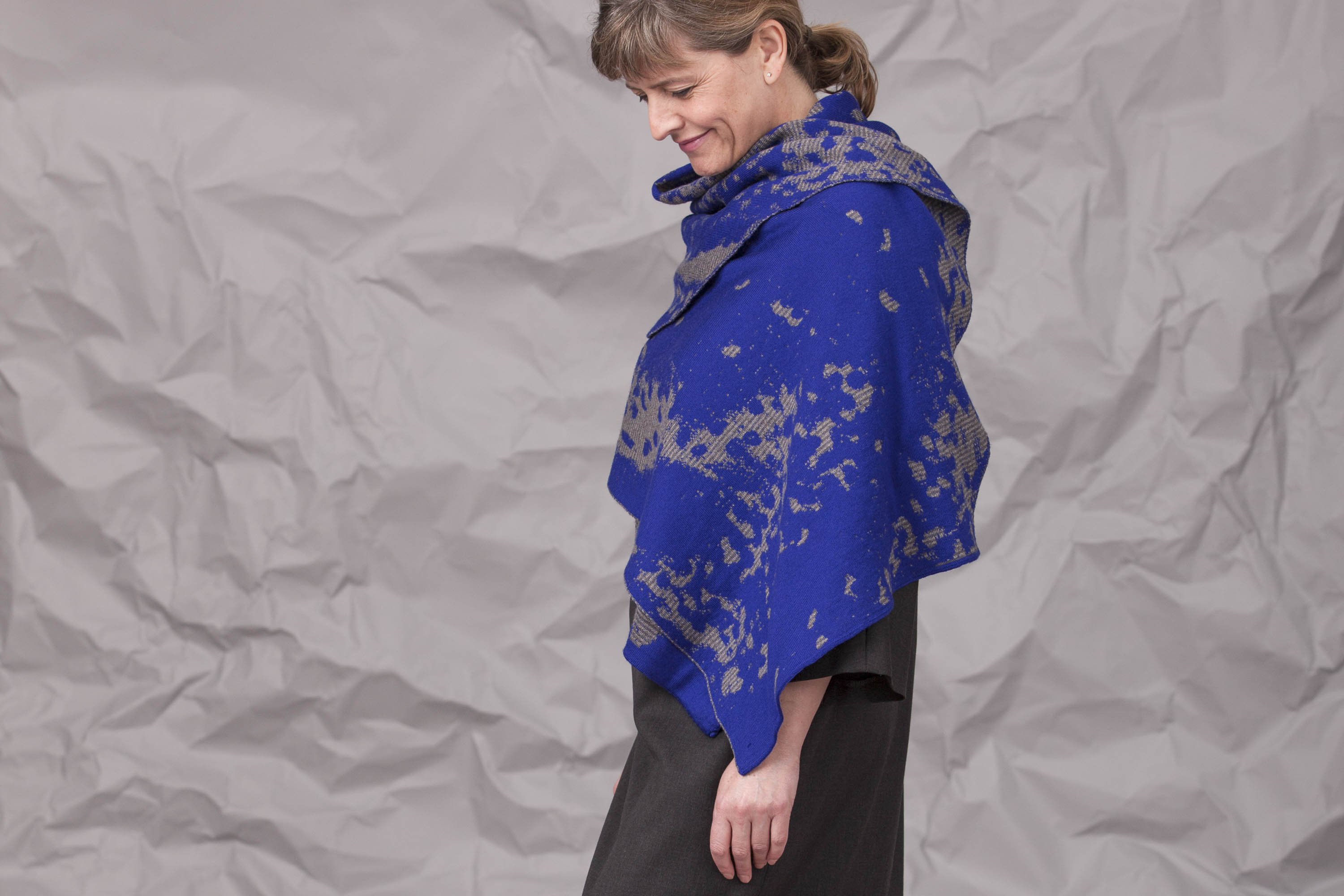 Modern Shetland shawl worn over a charcoal grey fine wool dress. Model stands side on with abstract knitted wrap in Yves Klein blue and greys