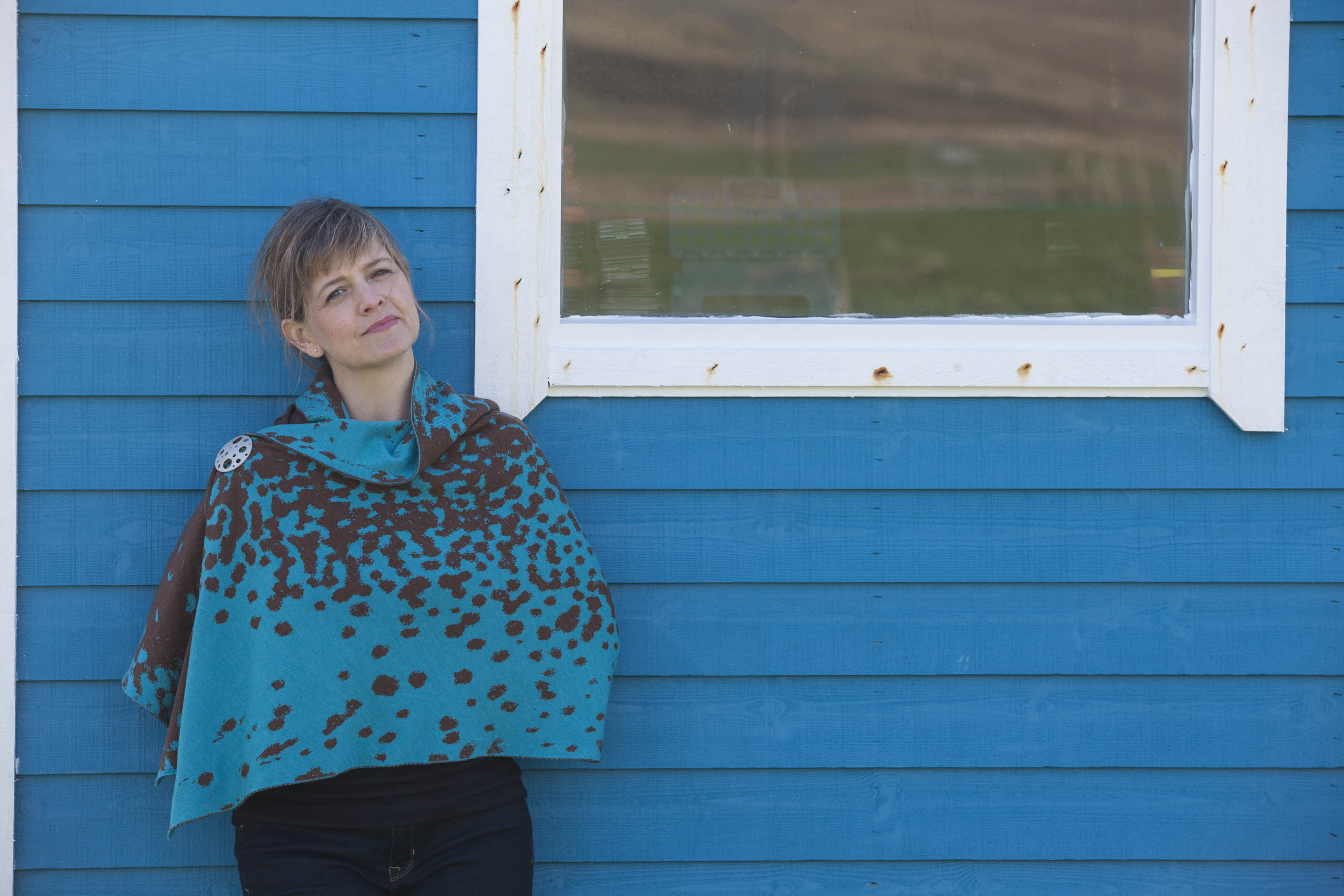 Woman stands against a blue, wooden shed. She wears jeans and a fine knitted contemporary Shetland shawl in an abstract mottled pattern - in a deep turquoise blue and bronze.