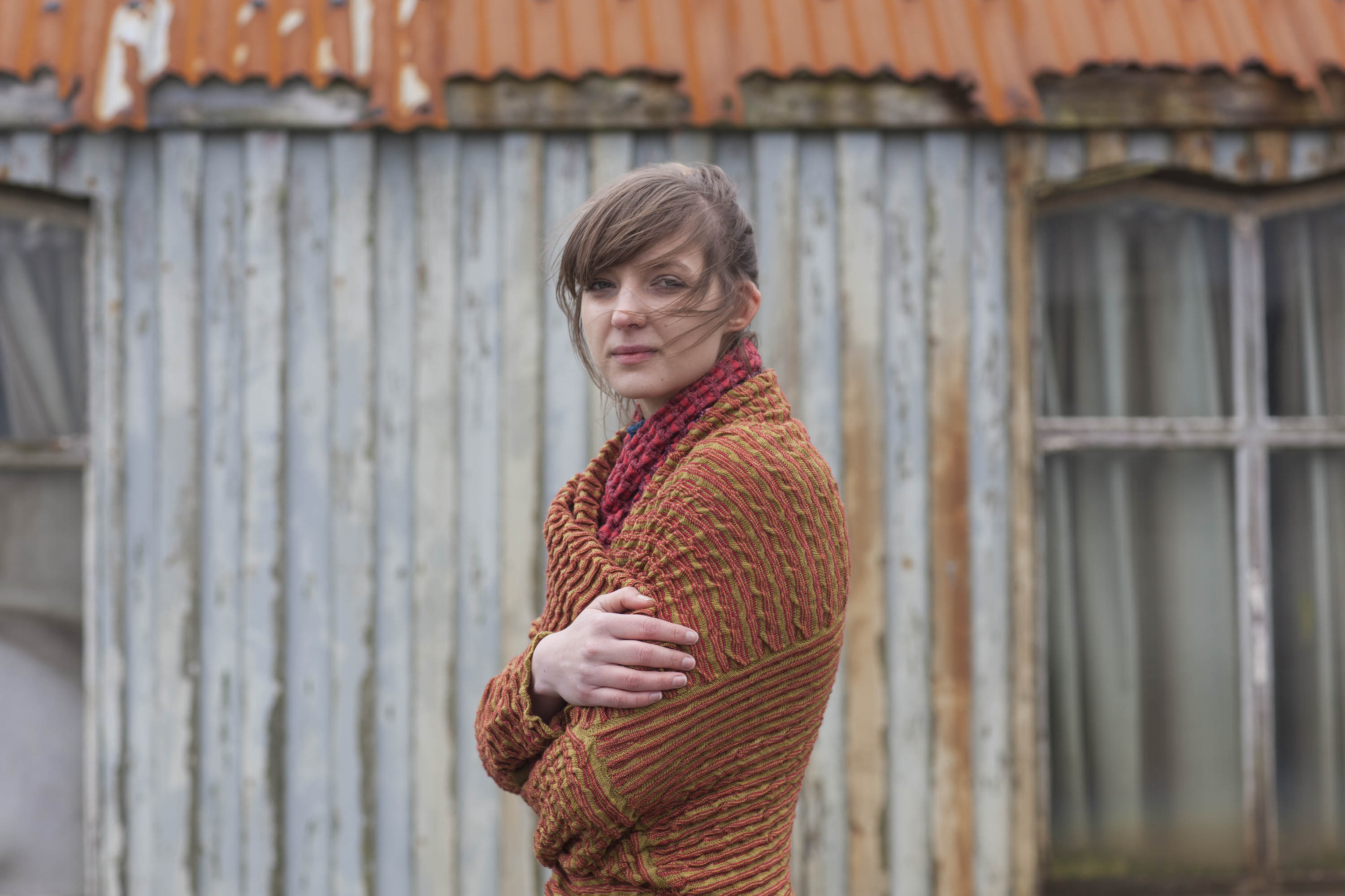 Model wears ridged, knitted jacket in rust colours. She stands in front of an old wooden building - The Gospel Hall at Hoswick, Shetland, which has a rusted tin roof.