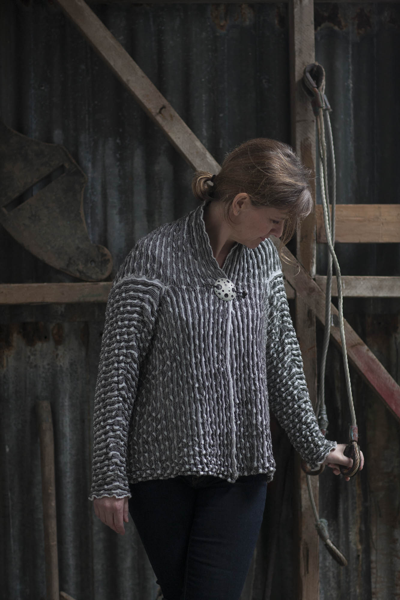 Modern Shetland knitwear - model wears ridged knitted jacket in chalky white and greys, pinned at neck