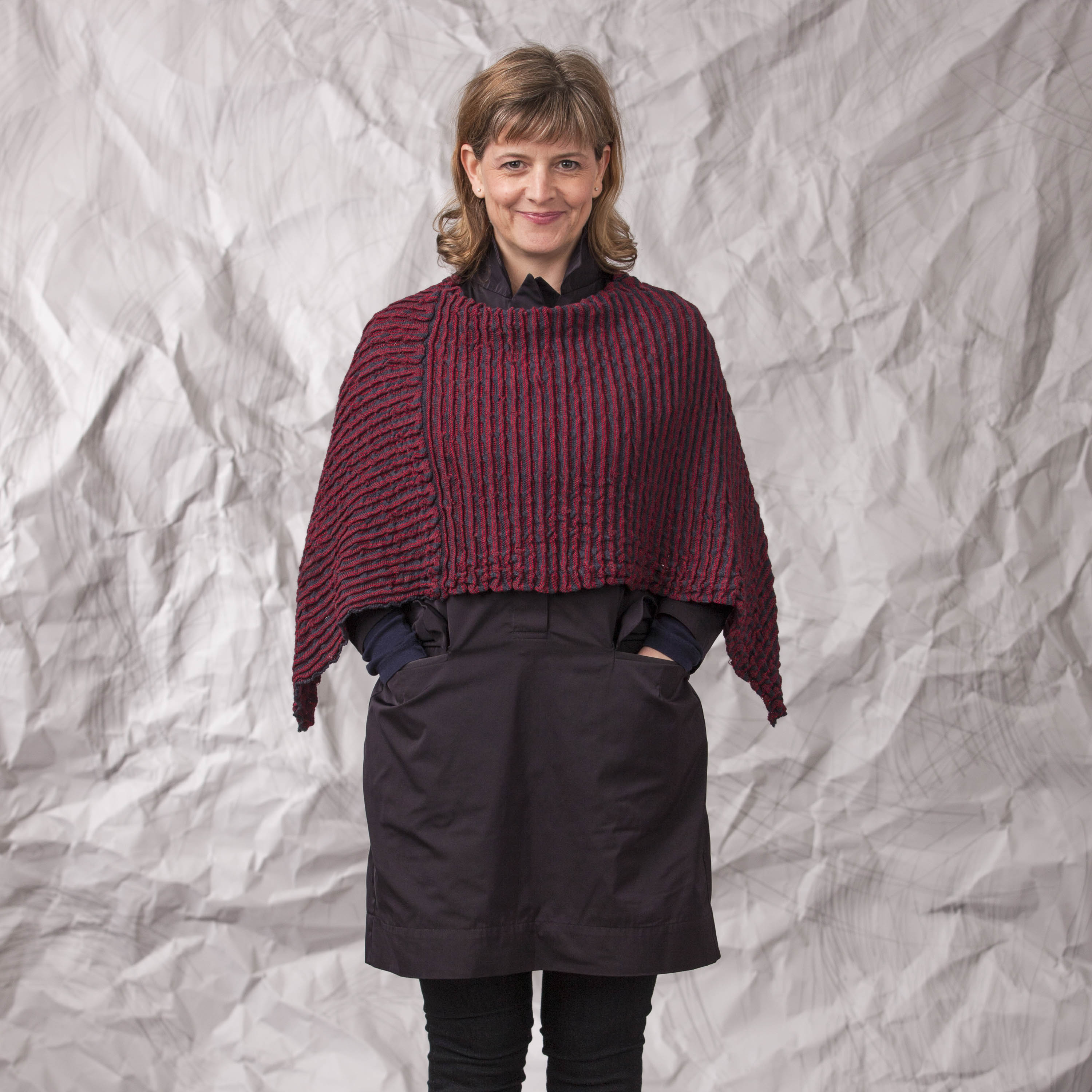 Contemporary Scottish knitwear, poncho in gently ridged fabric in dark berry coloured. Worn by a woman, over a navy shirt dress