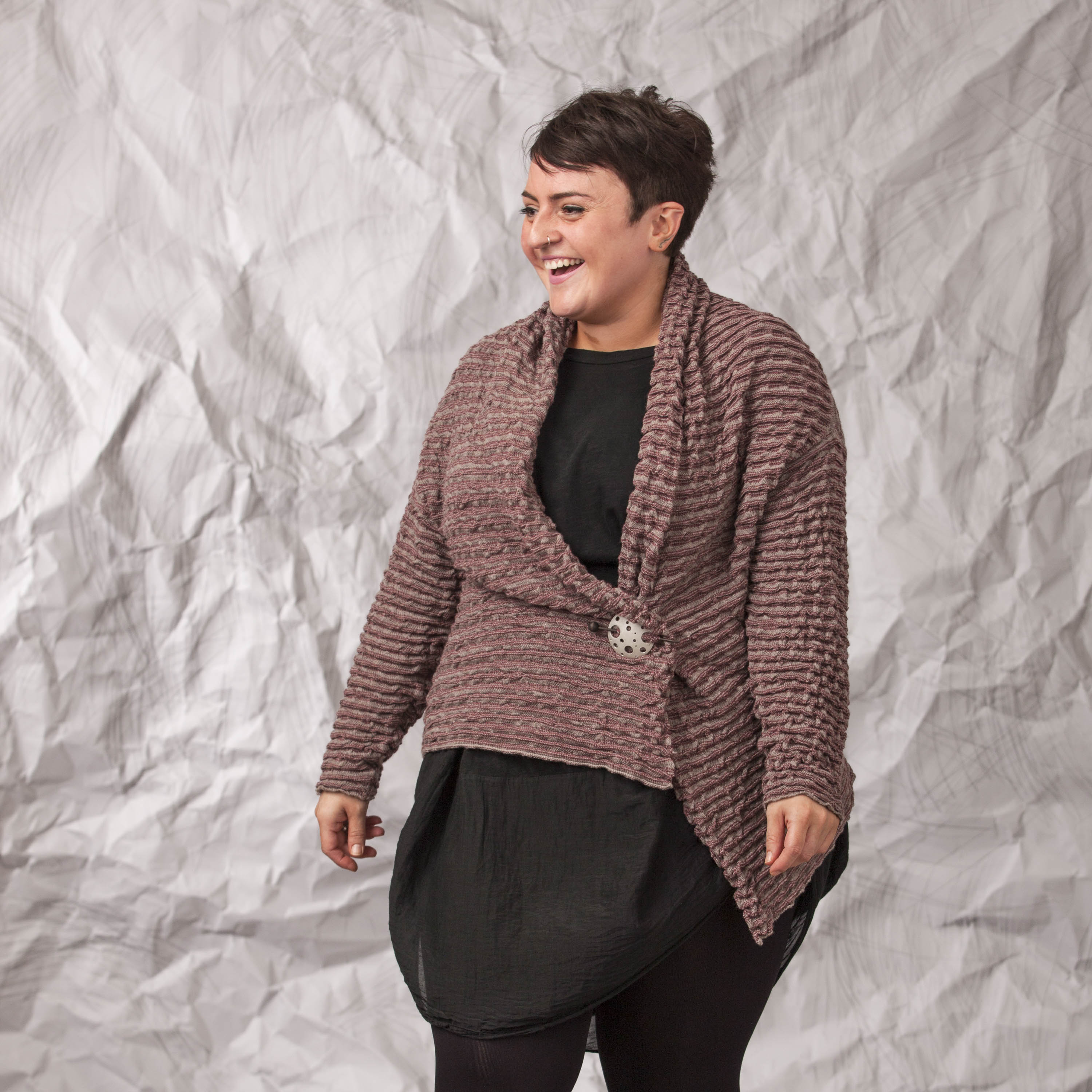 Model wears a long Vaarie Jacket in warm grey and morello over a black dress. The jacket is a slouchy open cardigan in a softly ridged, textural knit.