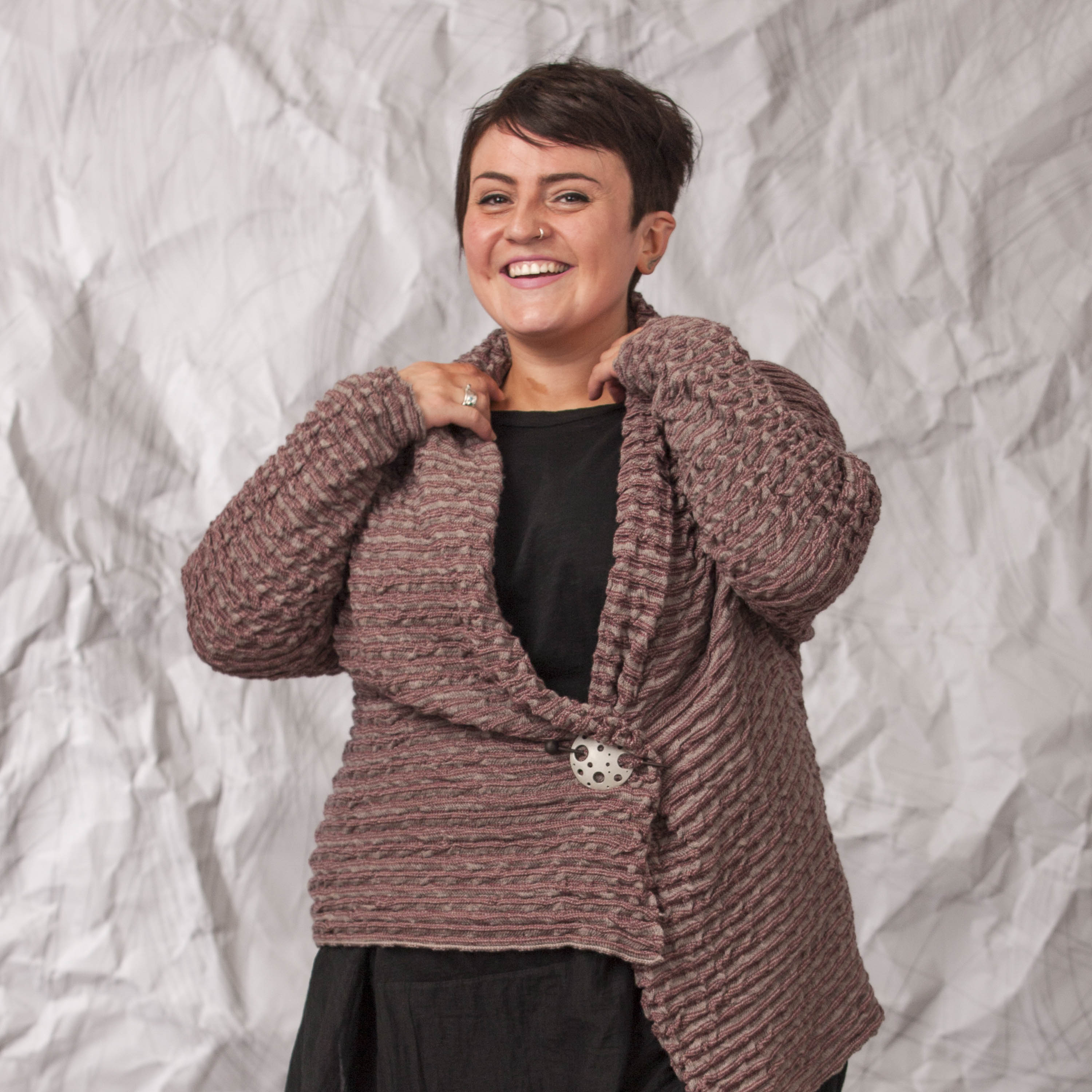 Model wears a cherry and warm beige jacket, with pin. The cardigan is textured with soft ridges and a cowl neck. She also wears a loose, black dress.
