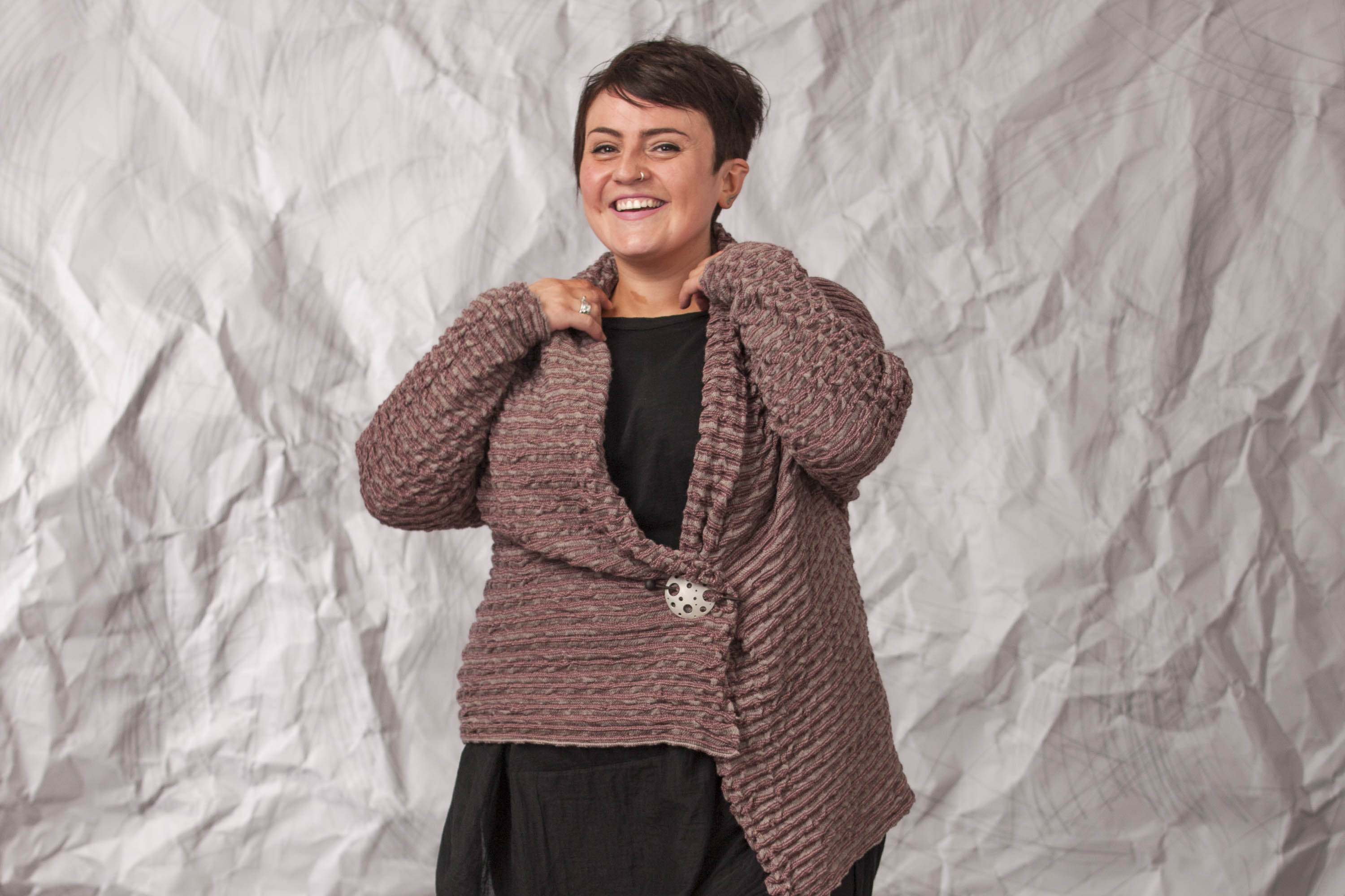 A softly ridged, warm grey open cardigan is worn over a black dress and fastened with a silver pin.