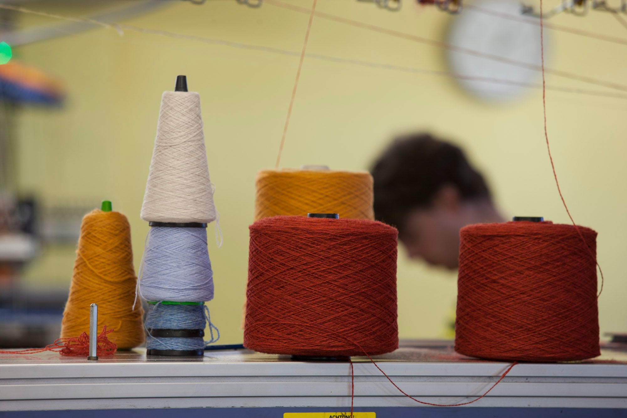 In the knit room at Laurence Odie, Hoswick, Shetland. Cones of red, orange, blue, and cream yarn on top of a knitting machine, with a technician in the background