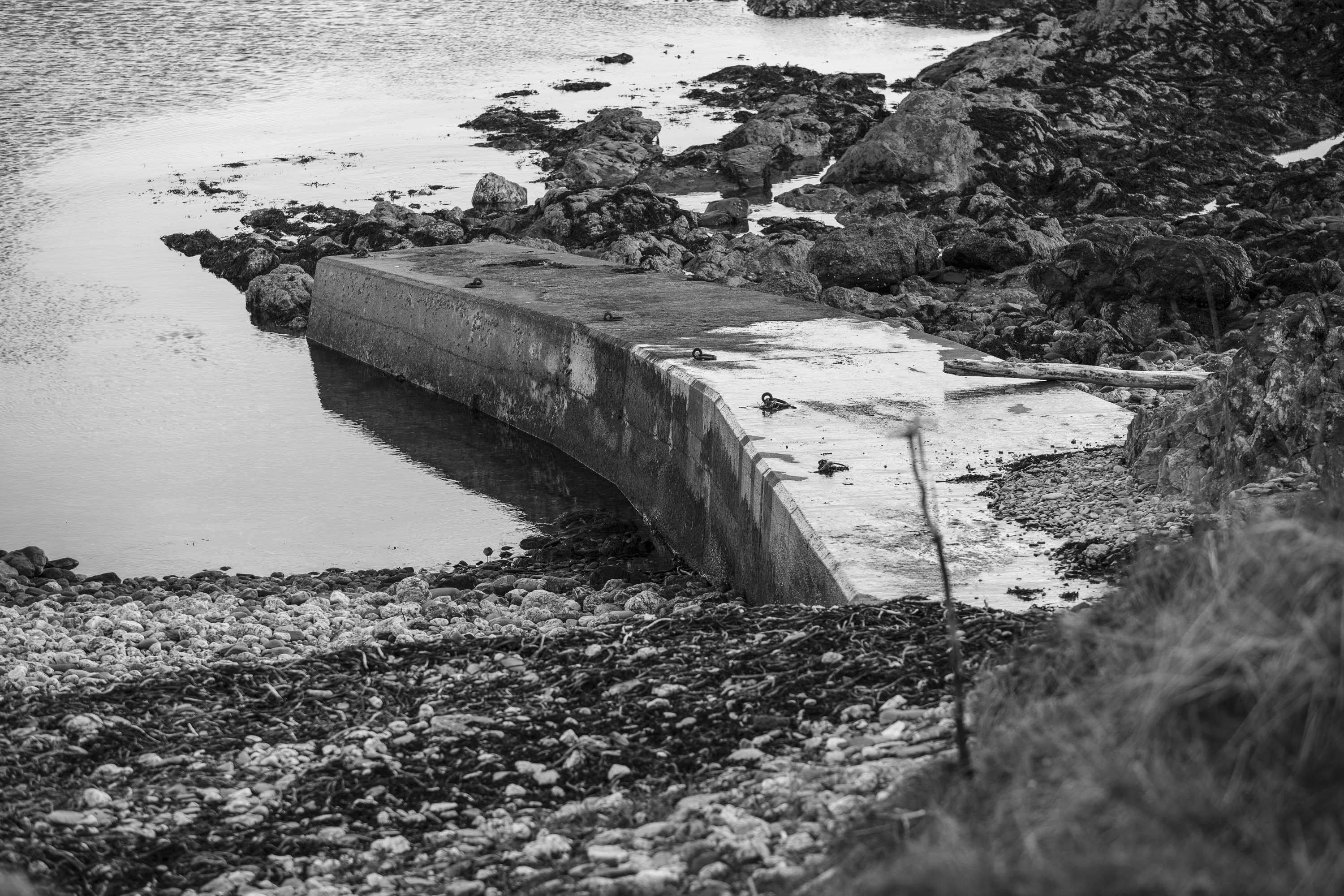 View onto the shore at Hoswick, Shetland. The small pier cuts into the sea and lines of seaweed are shown washed up on the stones. Behind the pier, the shore becomes rocky.