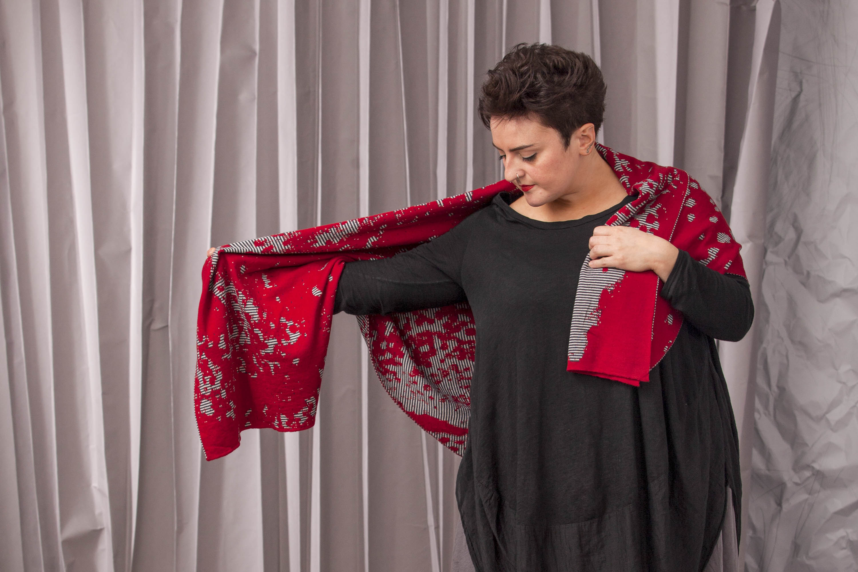 A woman in a loose, black dress wears a large abstract patterned modern Shetland shawl in reds and greys