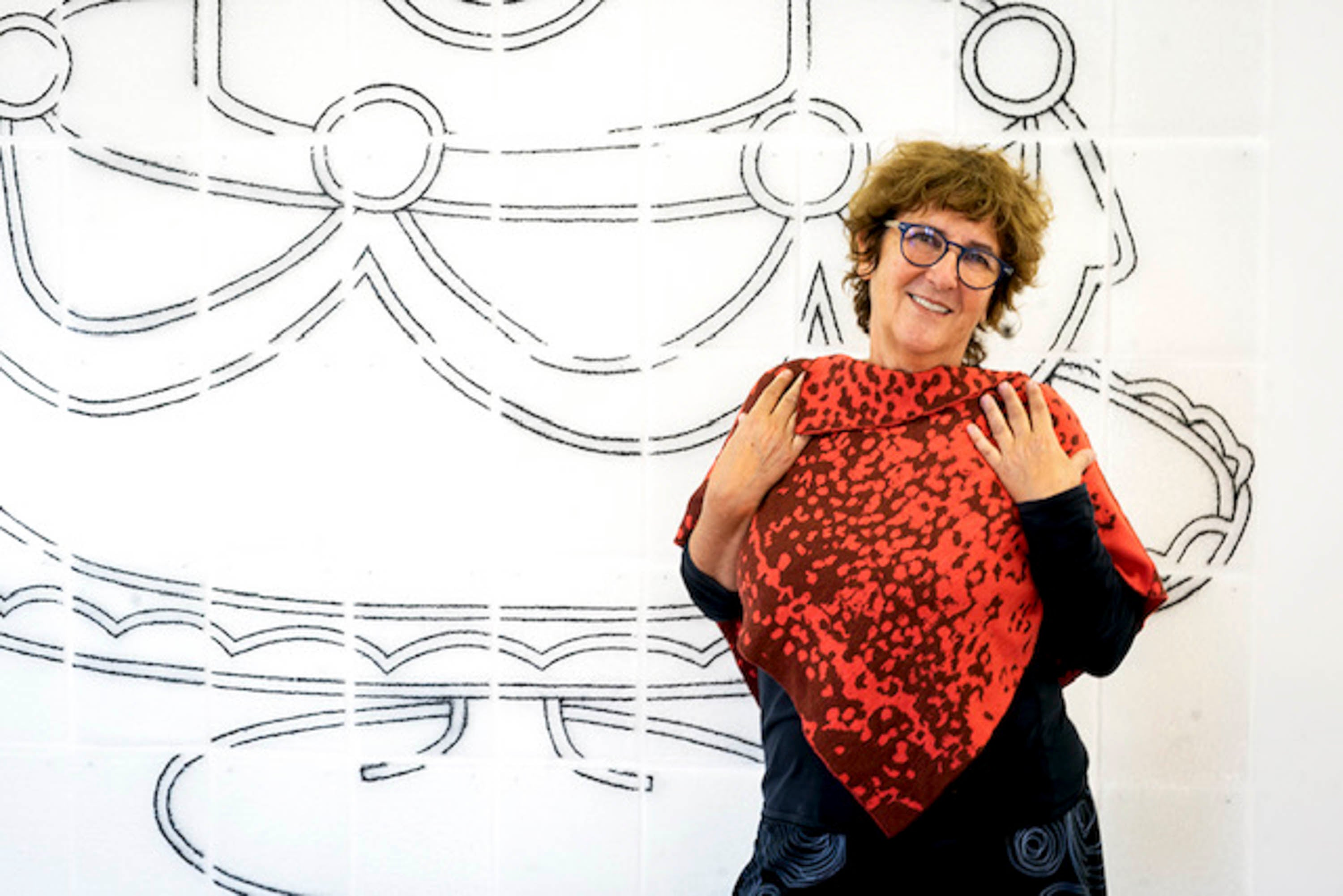 A woman stands against an abstract mural, wearing a cape in two rust colours. She holds her arms up to her collar bone