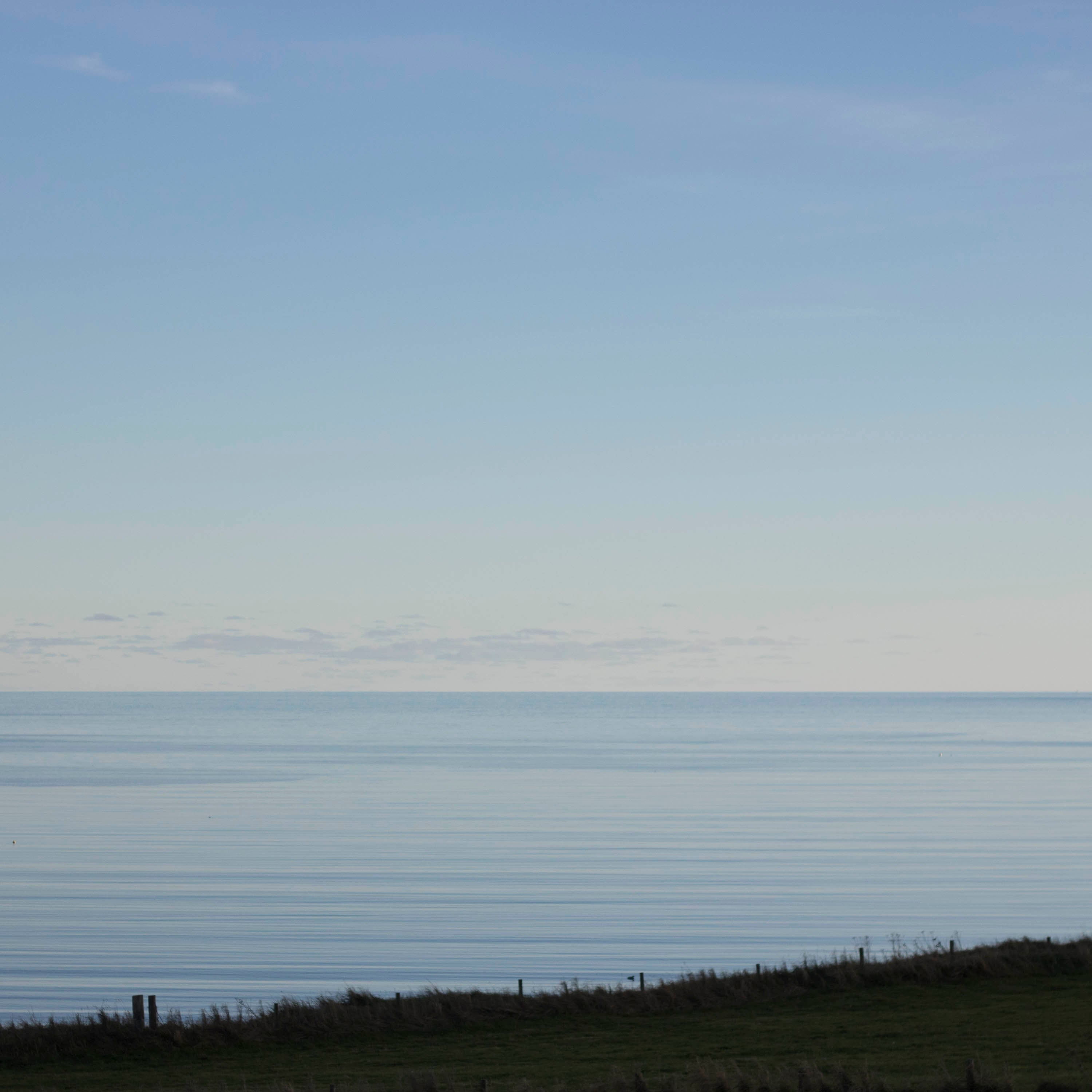 Looking out over a grassy field, at twilight, to a very still sea at Hoswick, Shetland