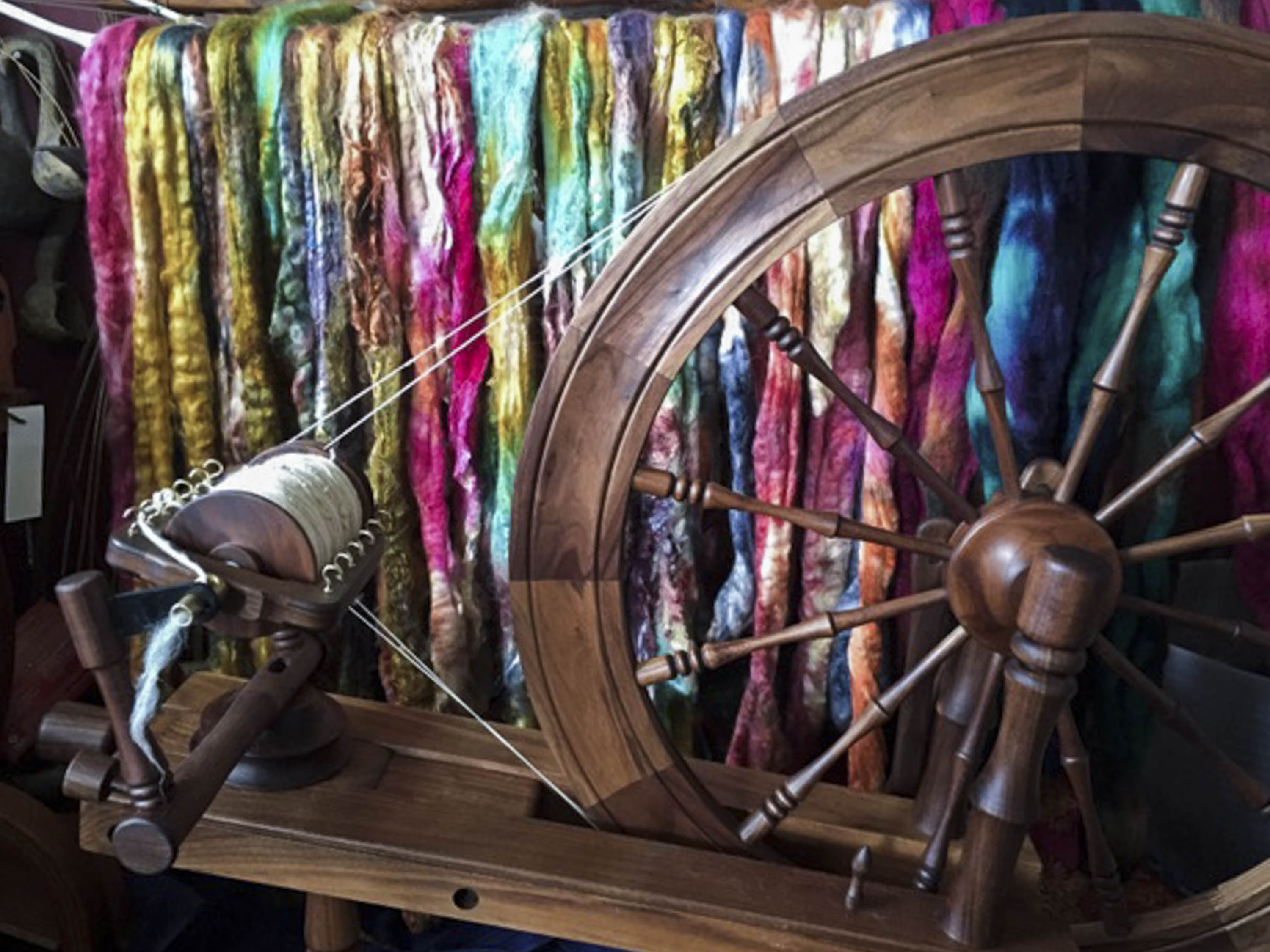 A wooden spinning wheel in front of brightly coloured, dyed fibre, drying