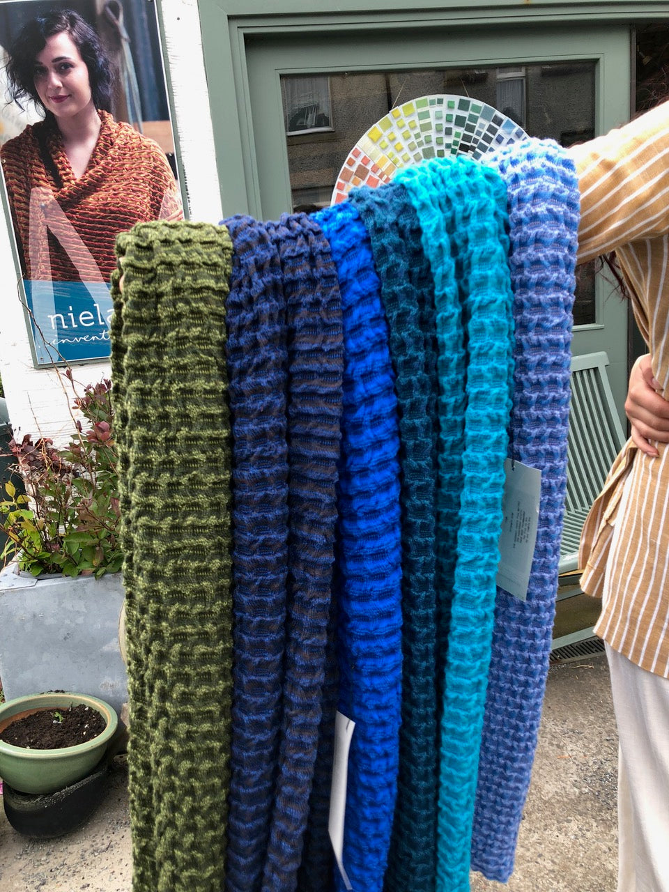 Holding out an armful of Rigg wrap scarves, outside the Nielanell contemporary knitwear studio, Shetland.
