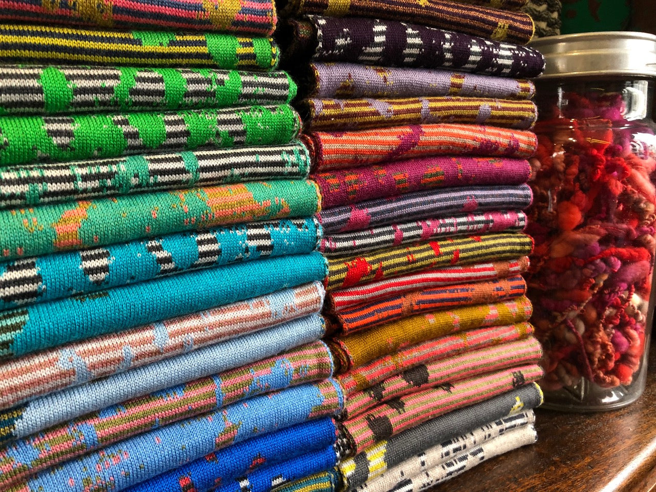 Stacks of contemporary Scottish knitwear - scarves - at the Nielanell studio shop in Hoswick, Shetland