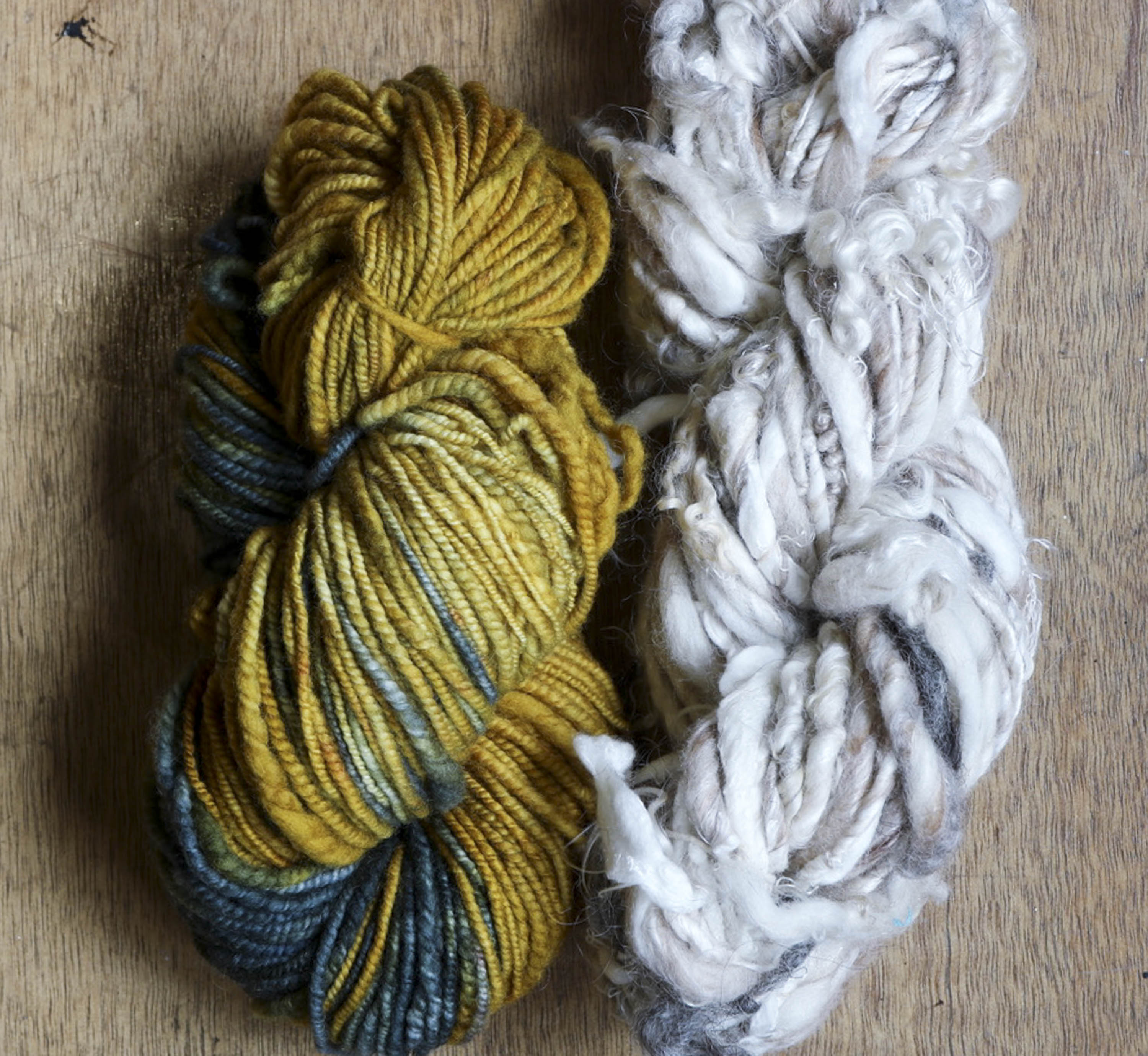 Two skeins of handspun art yarn. One in yellows and teals, the other in natural, pale greys