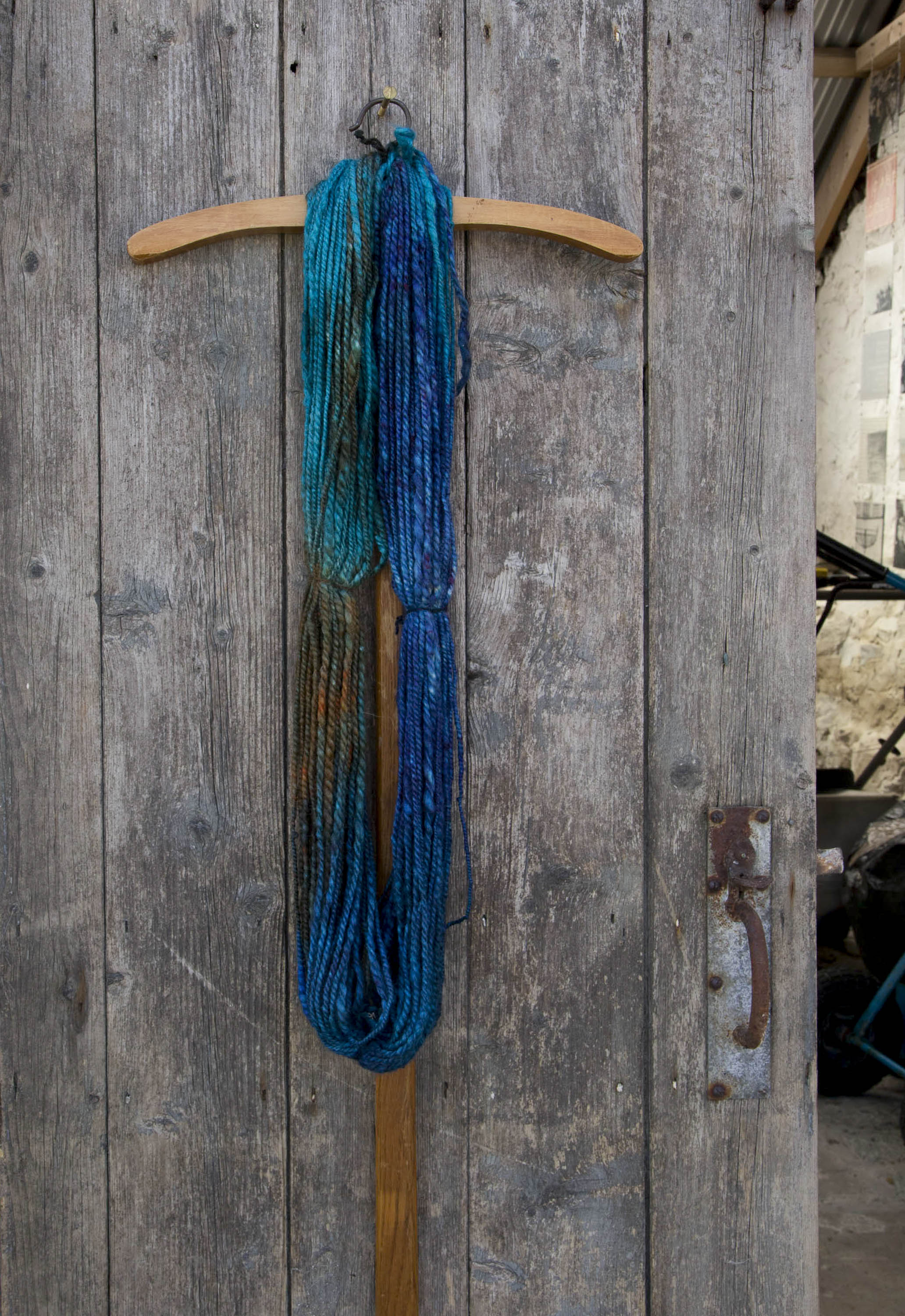 Handspun, hand-dyed art yarn made in Shetland by Niela Nell Kalra. A hank of yarn hangs on a weathered wooden door, with a glimpse inside a stone built traditional Shetland croft house.