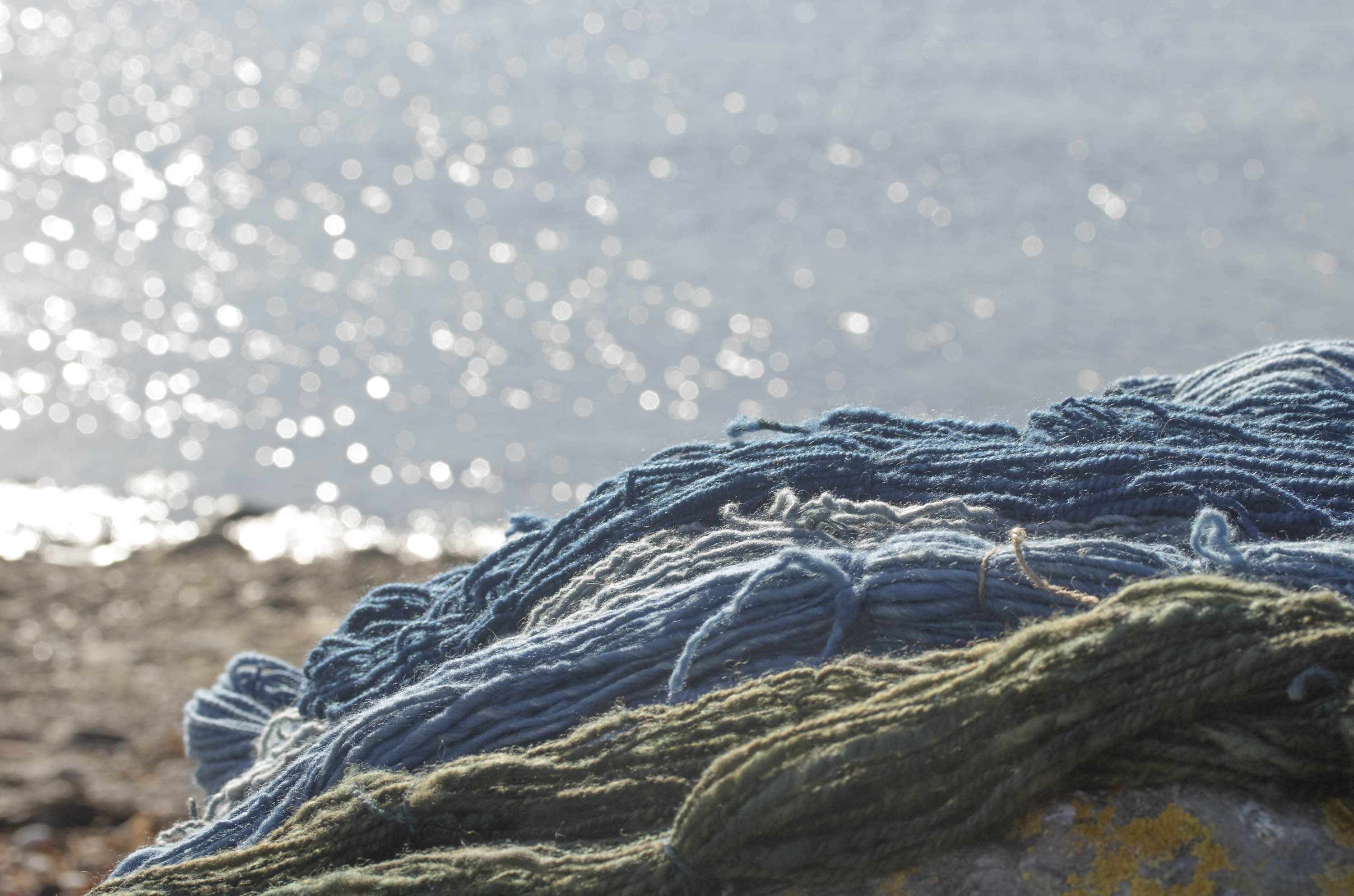skeins of handspun yarn on a rock on the shore at Hoswick, Shetland, with a sparkling sea in the background